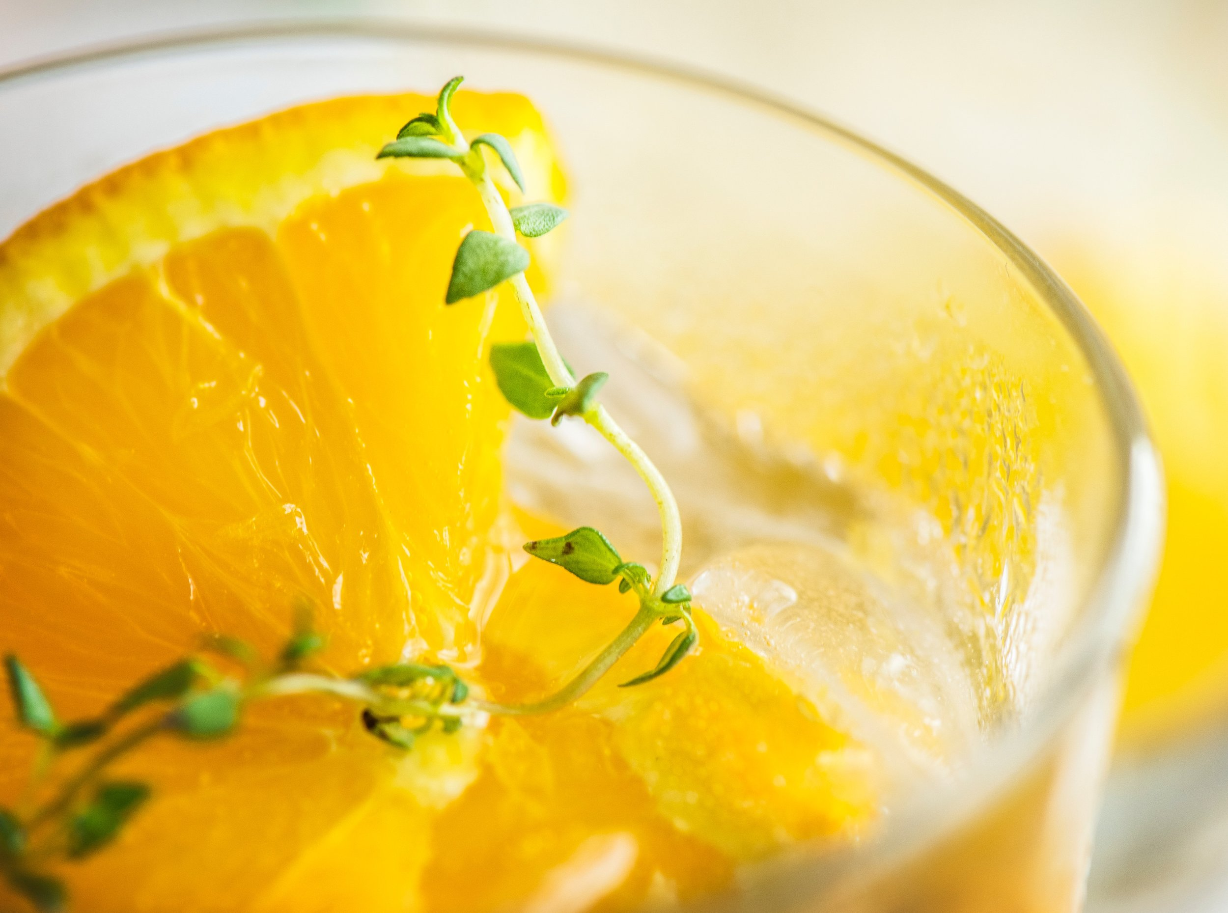 A glass of orange juice garnished with fresh thyme leaves