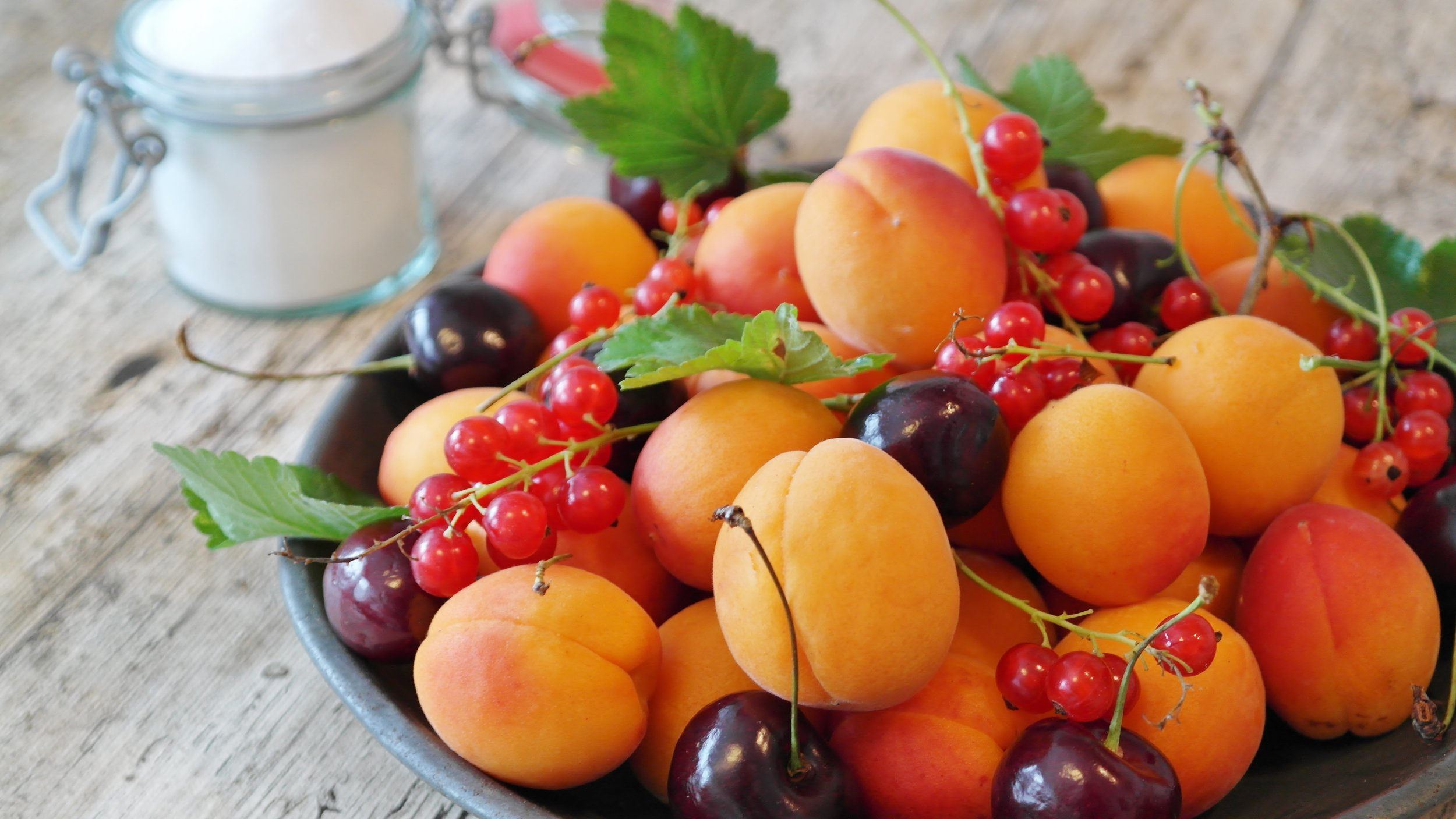 A platter of fresh apricots, cherries and red currants on a rustic wooden table