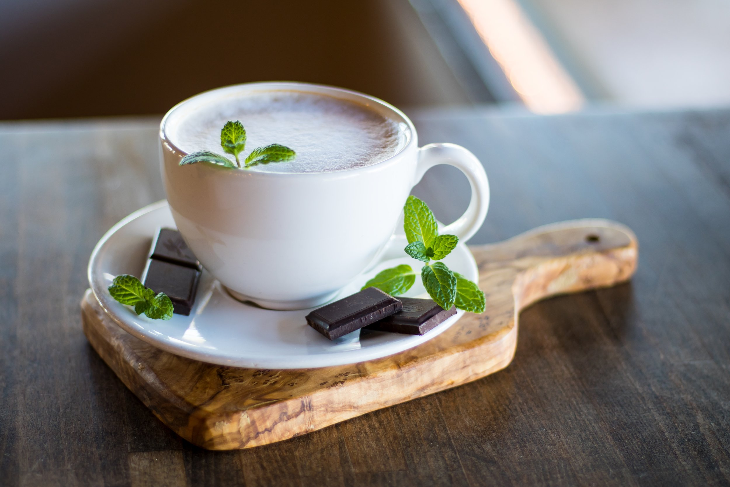 Peppermint leaves garnish a cup of hot chocolate