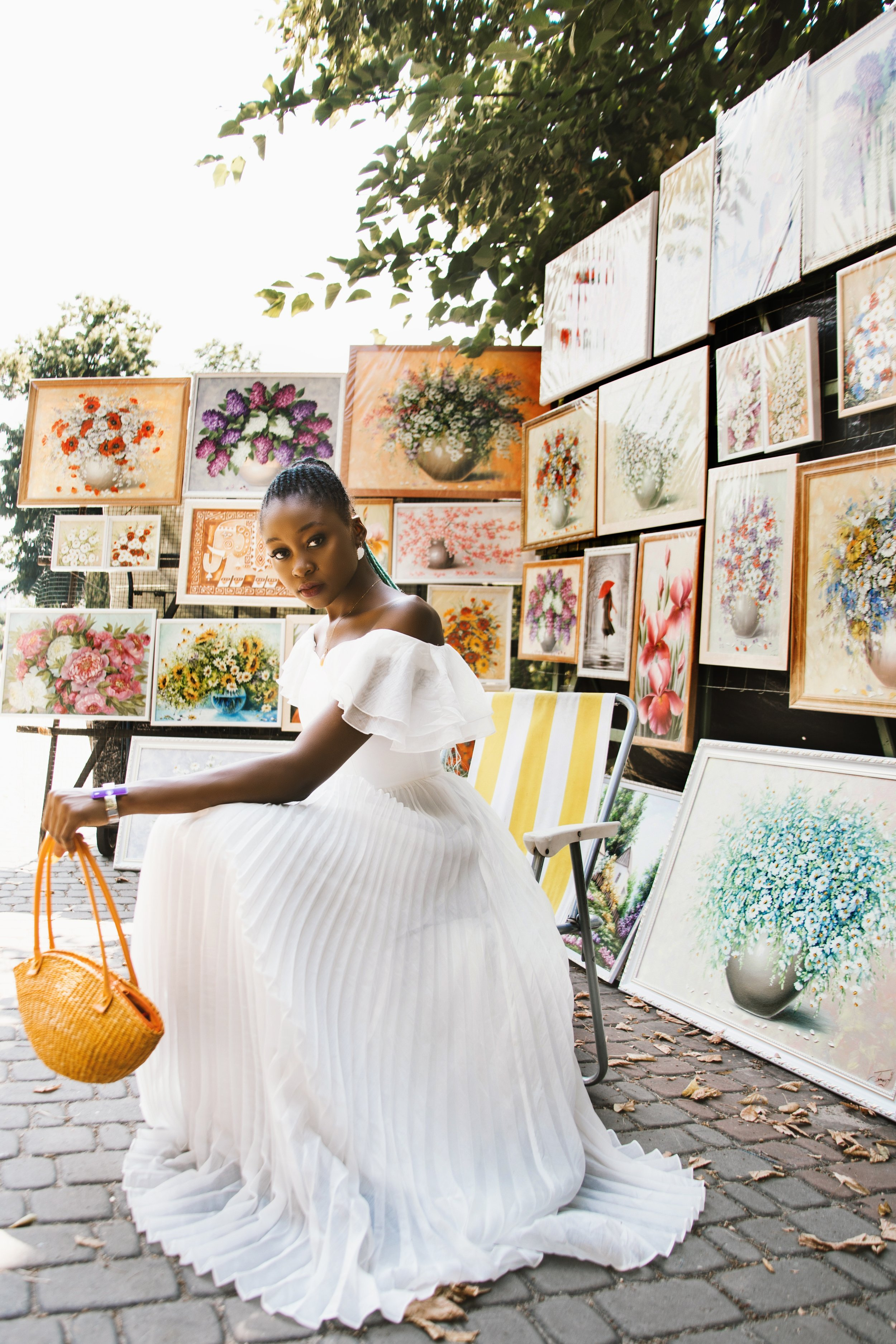 A beautiful woman in a white pleated gown holding a gold toned wicker purse sits in front of a street art exhibit