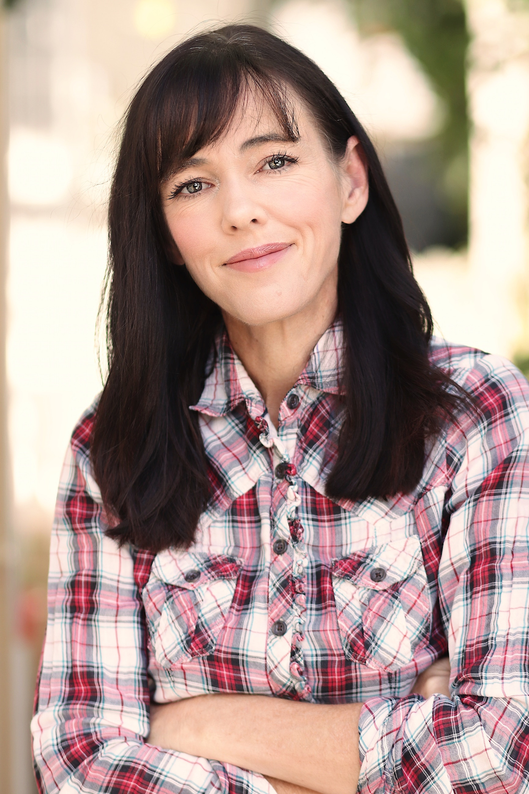 A beautiful middle-aged woman in a plaid flannel shirt