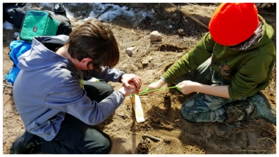 Two students working on a tag-team primitive bow-drill fire