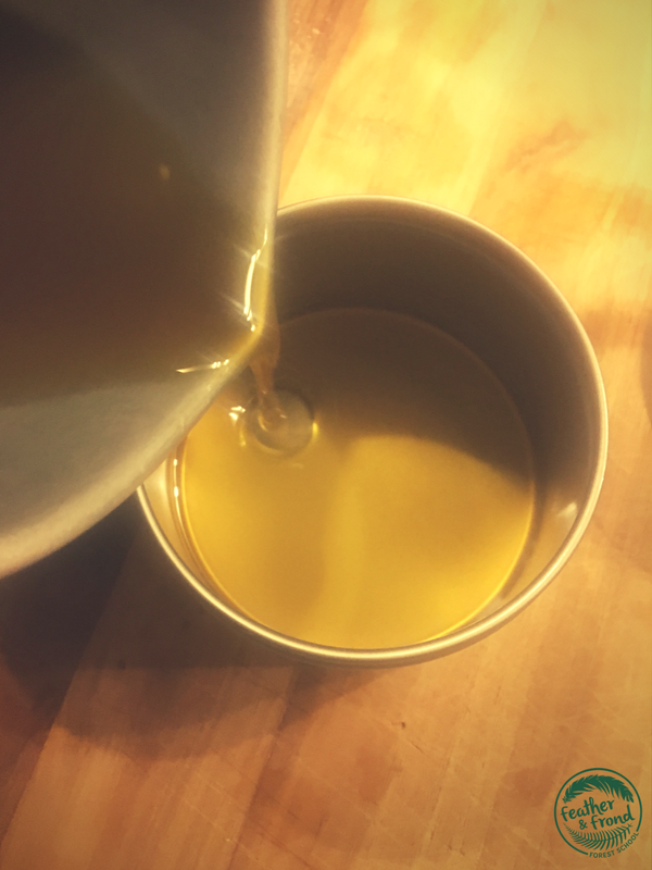 pouring the infused Plantain oil and beeswax mixture
