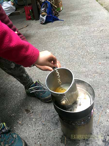 Dipping Cottonwood seed pods into melted beeswax to make candles!