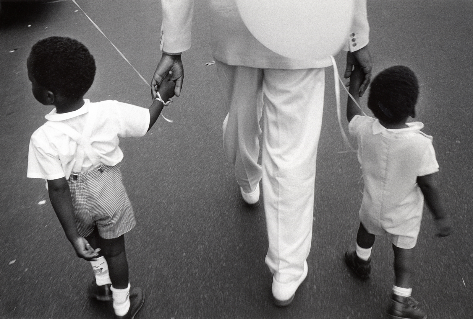 A father takes his two small sons to the Harlem Day Festival after church, 1988