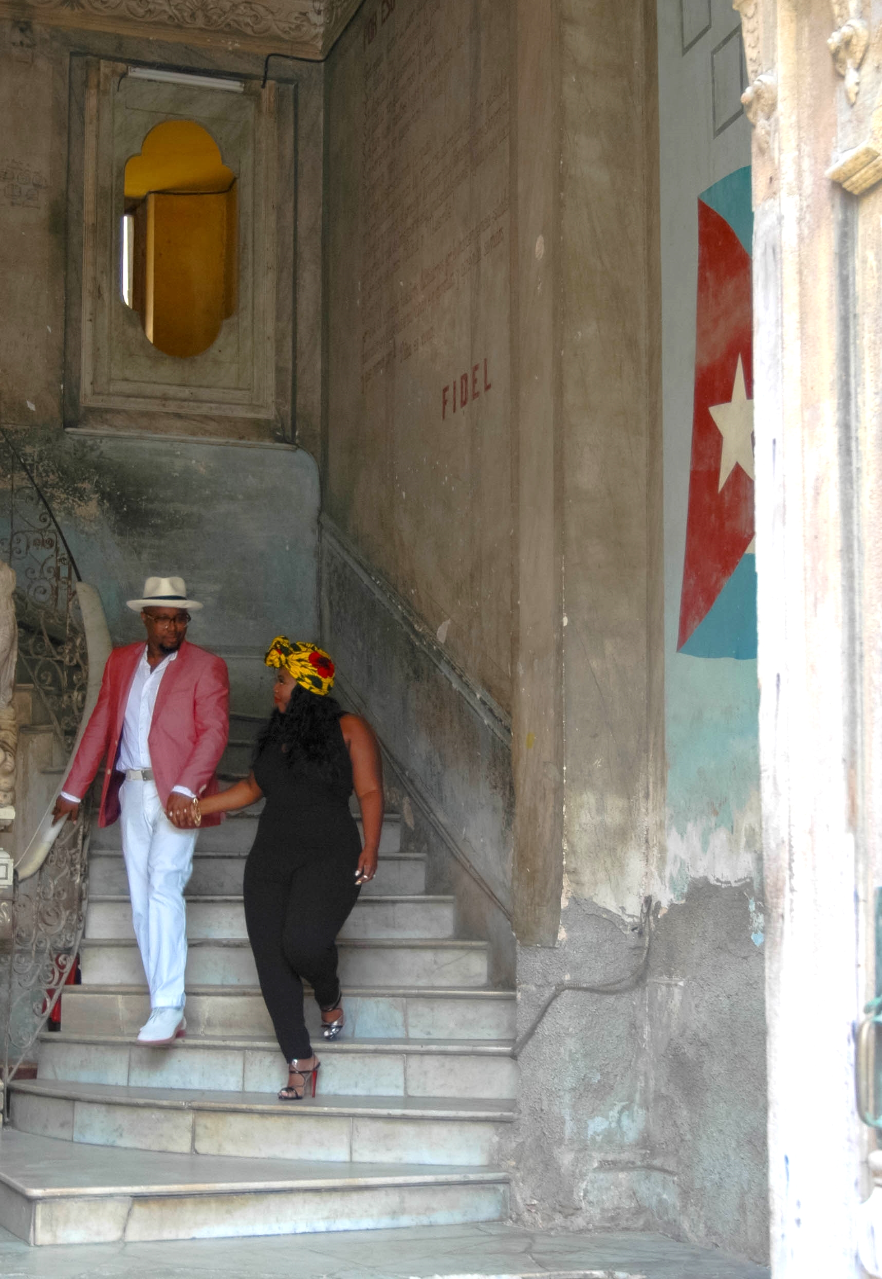 A couple poses for a photo amongst the remains of a marble staircase