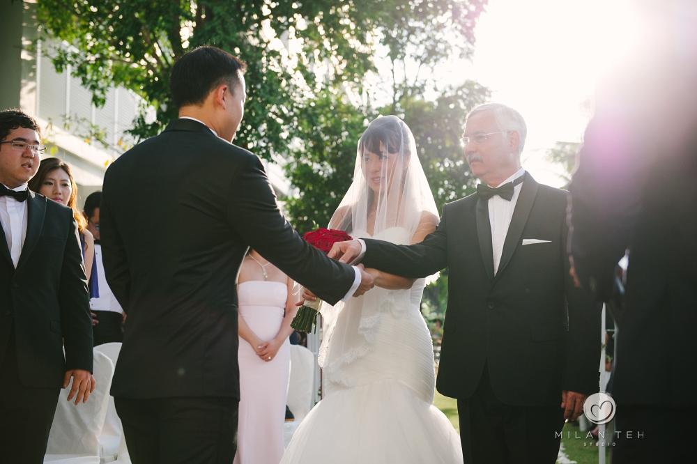 bride's father pass her hand to groom at penang e&o hotel garden wedding