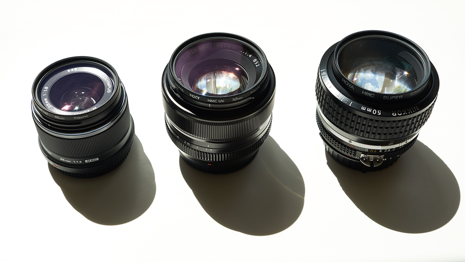Three lenses with the same angles of view but for different sized image sensors. L to R: Olympus 25mm f/1.8, Fujifilm XF 35mm f/1.4, Nikon AIS 50mm f/1.2