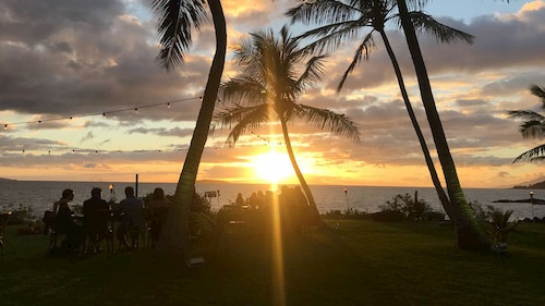 A group watching the perfect sunset in Maui island.