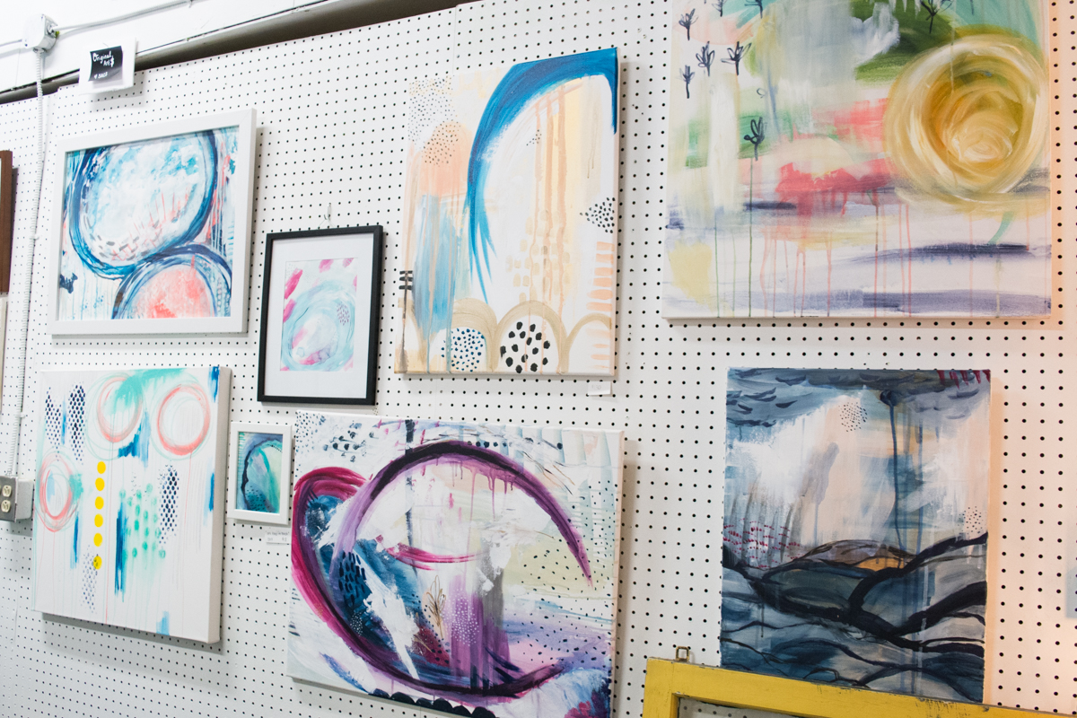 Jaci's studio wall filled with various abstract paintings.