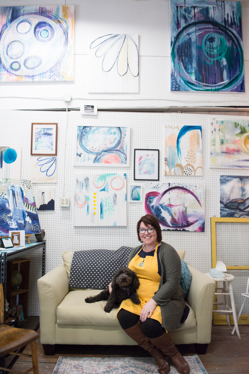 Jaci sitting in her studio with her dog Ellie. Behind them is a wall full of abstract paintings.