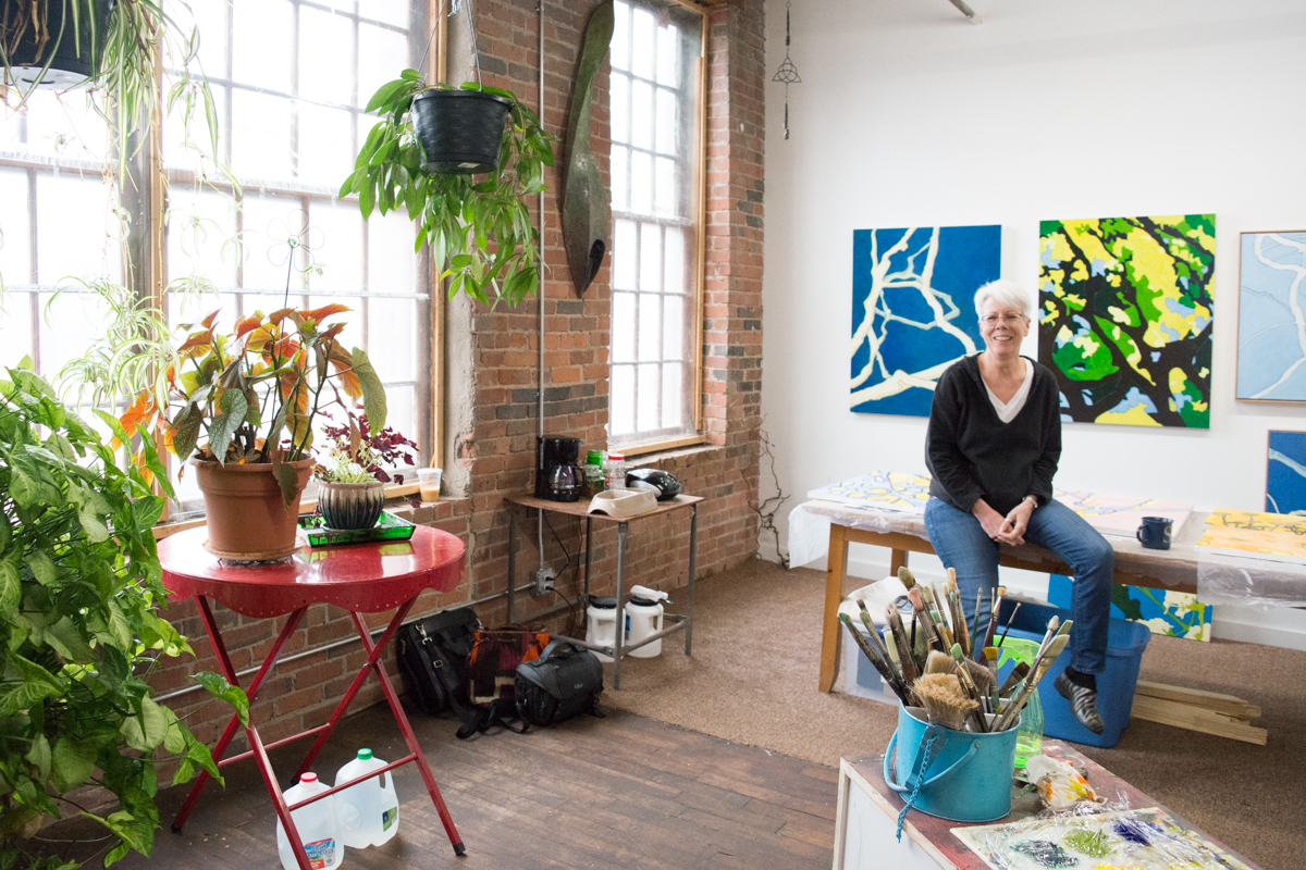 Steph sitting on her studio table surrounded by paintings and plants.