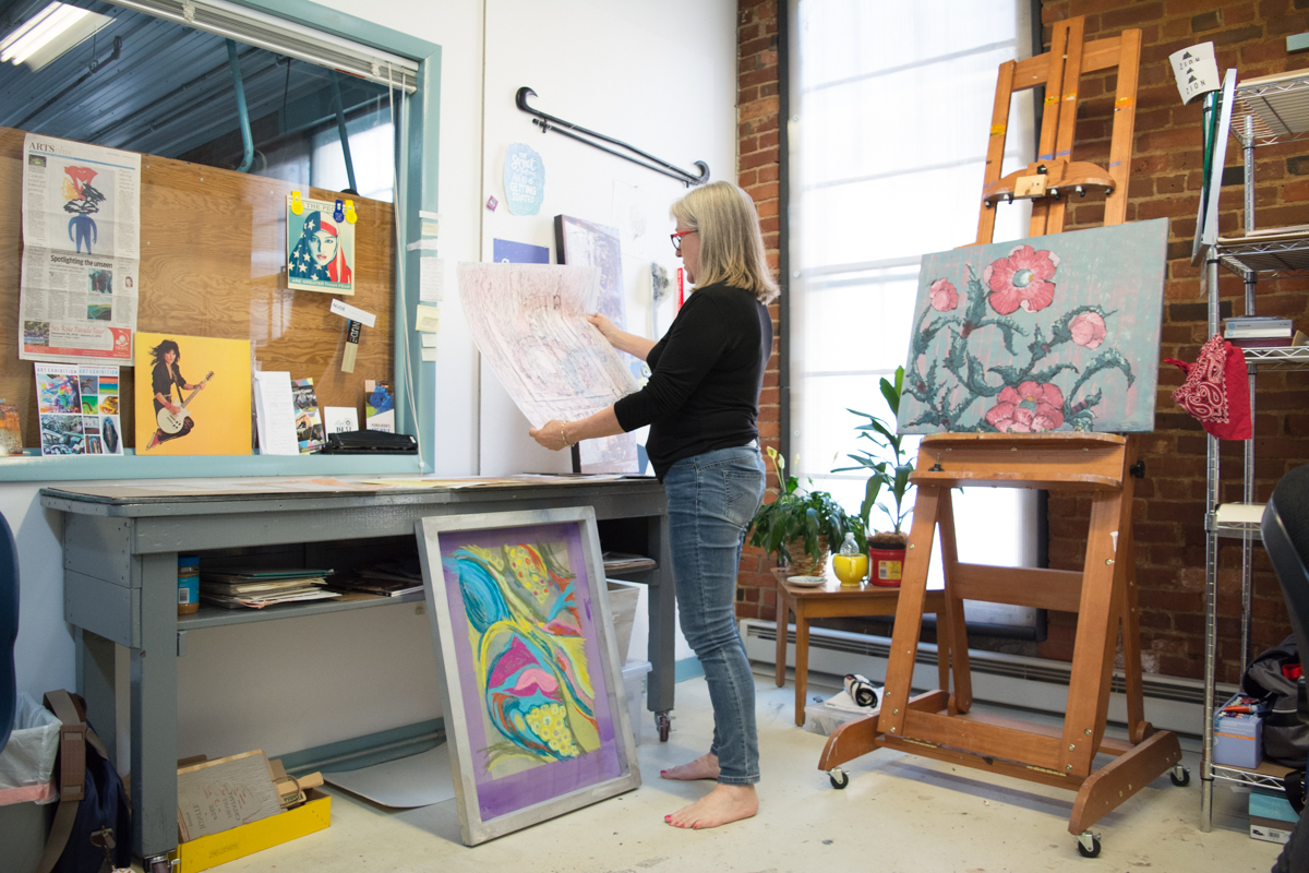 Barbie showing a newer piece while standing in her studio.