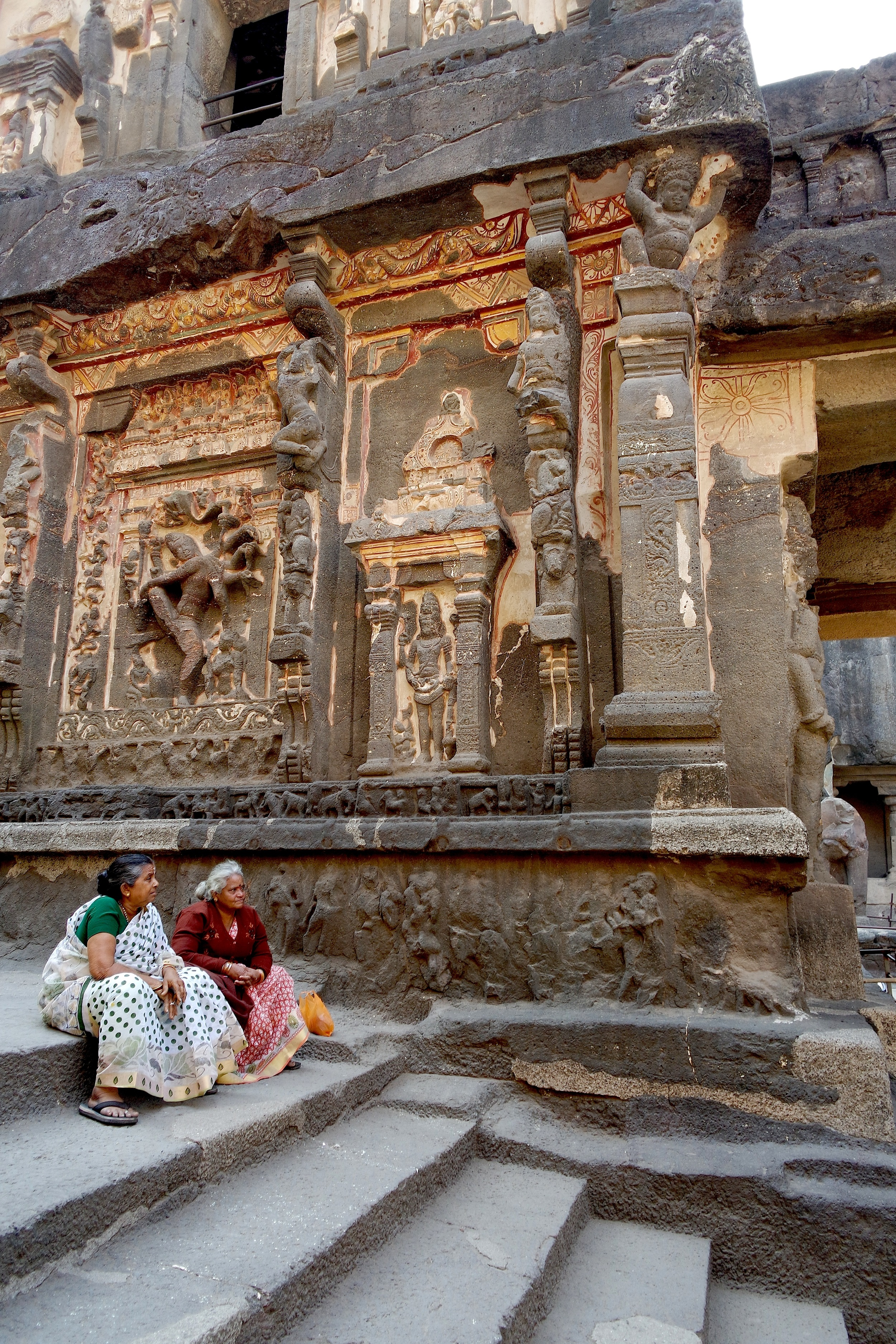 Two women sit on the steps of the massive Hindu temple at Ellora Caves in India