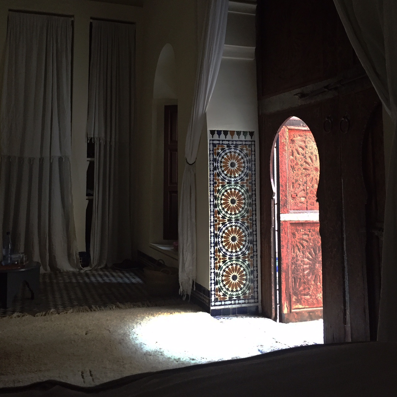Light from the courtyard spills into our room through the intricately carved door