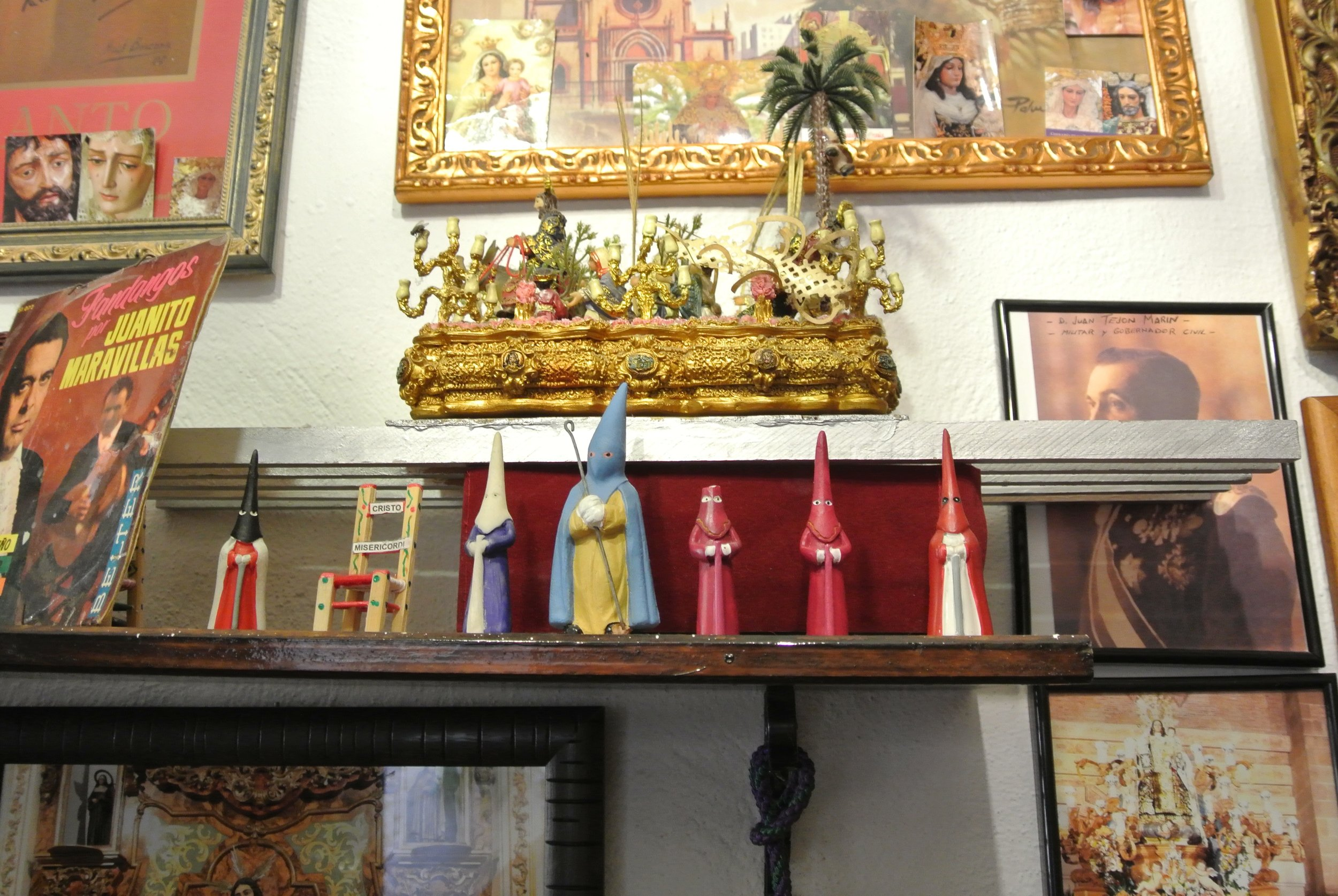 A shelf filled with nazareno figurines at Taberna Cofrade las Merchanas in Málaga. The different colored robes indicate which hermandad (brotherhood) the individual belongs to.