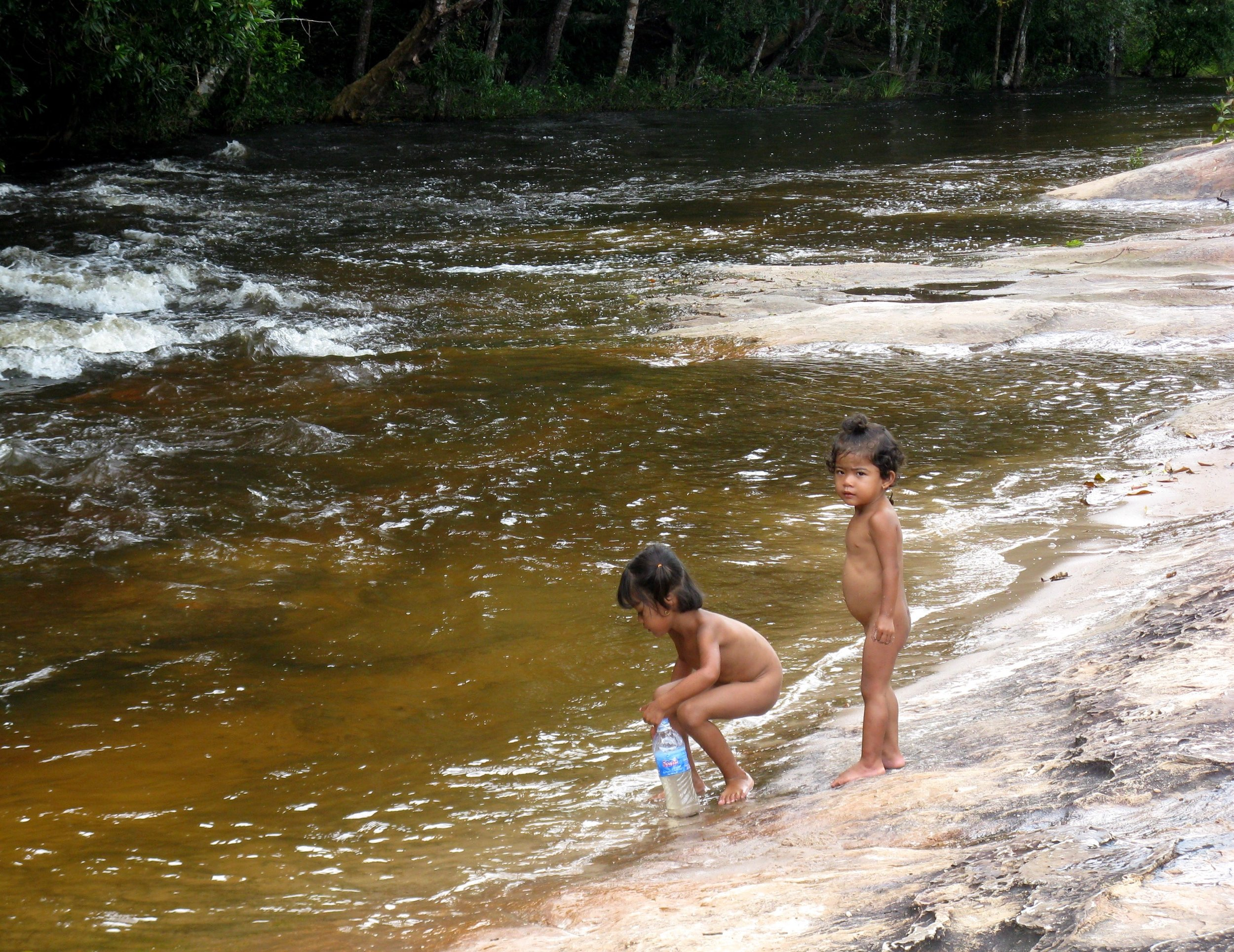Two young girls frolic on the bank of the Kbal Spean river