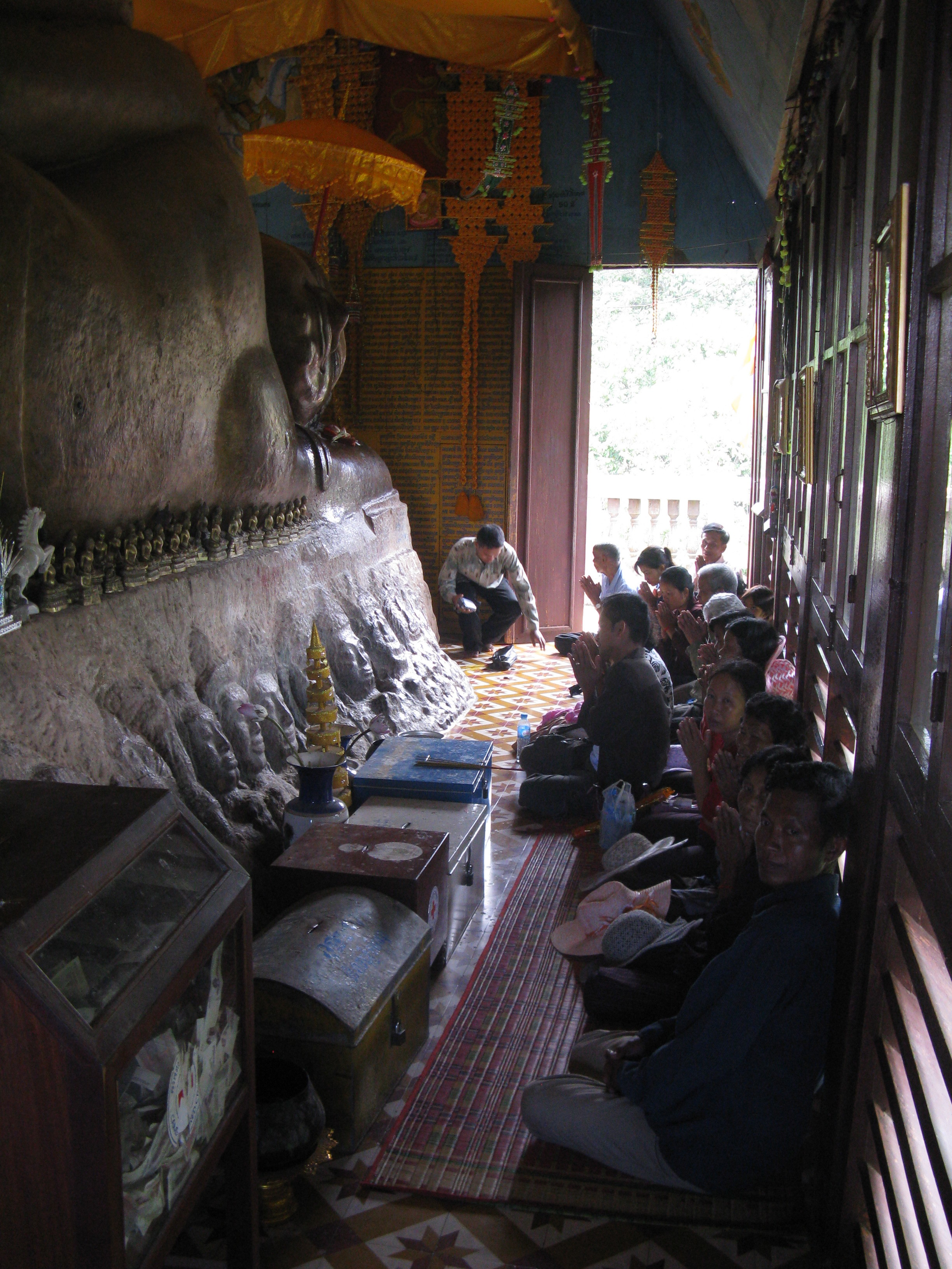 A large reclining Buddha carved out of the rock fills the temple at Preah Ang Thom