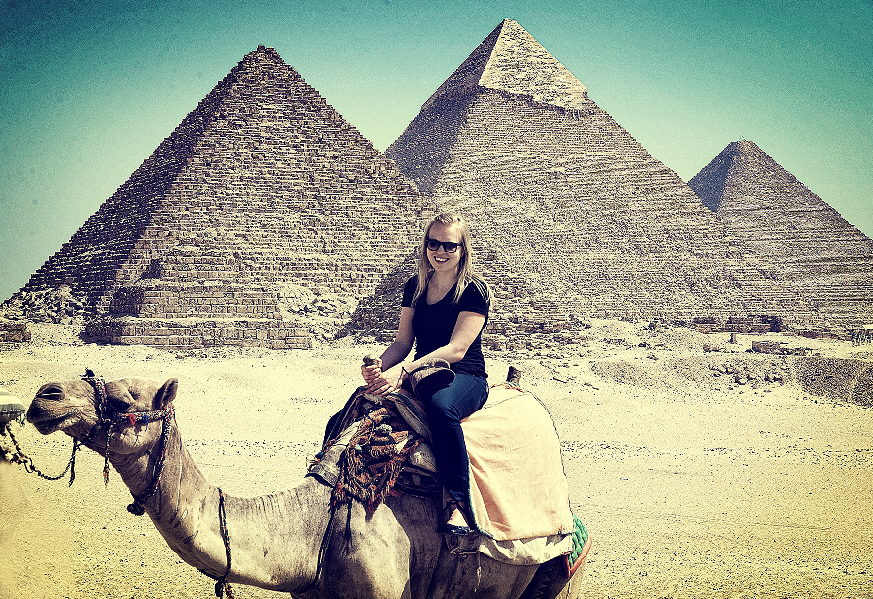 Margaret riding a camel at the Pyramids of Giza