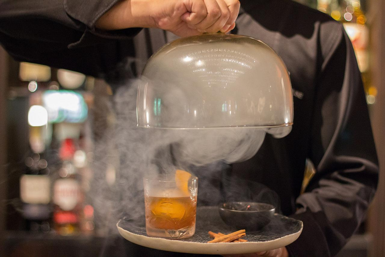 The Aged Teak cocktail is a take on an old-fashioned — but with cinnamon smoke in a cloche for a dramatic reveal