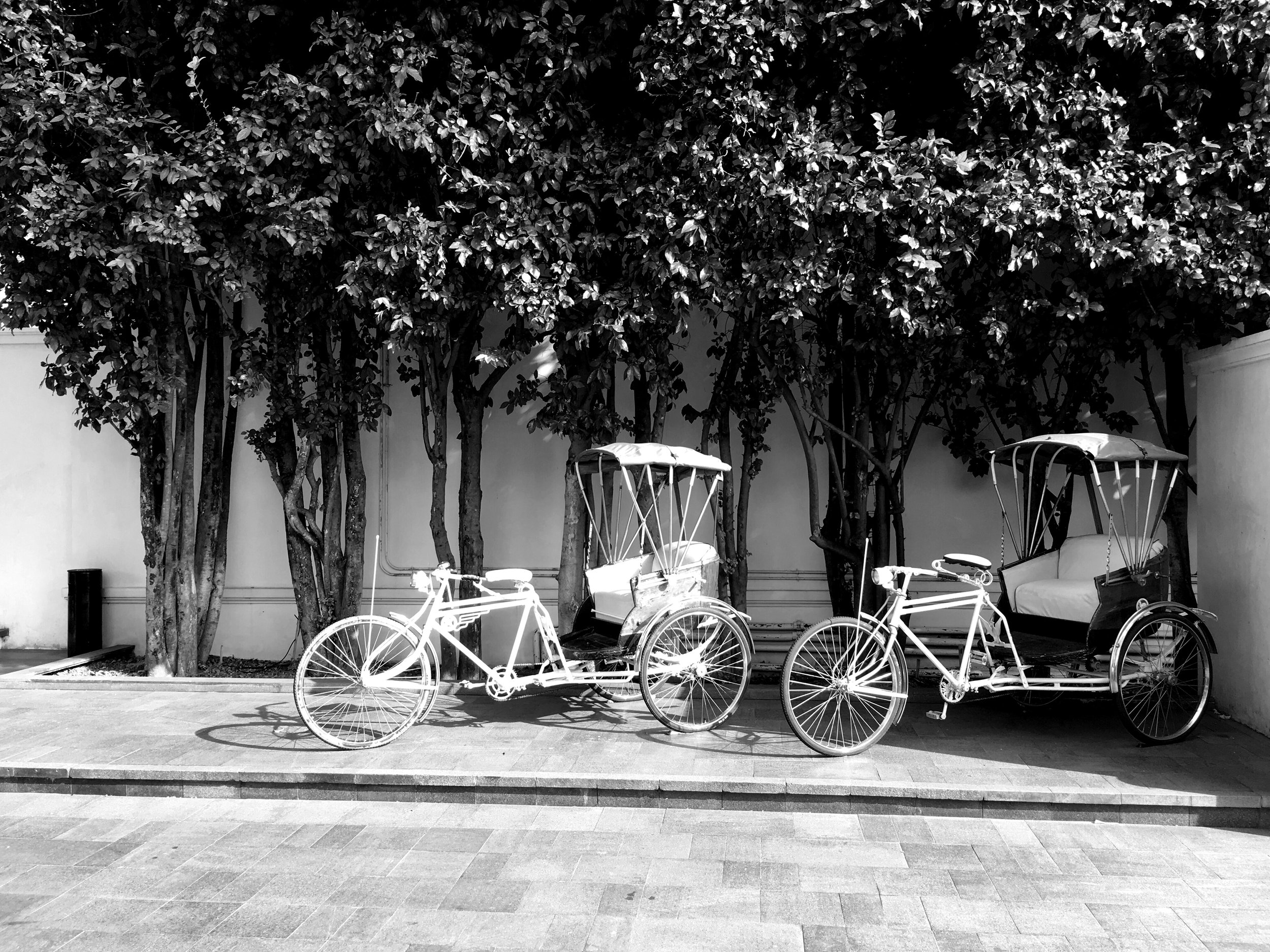 These bicycle tuk-tuks sit out front of the 137 Pillars hotel