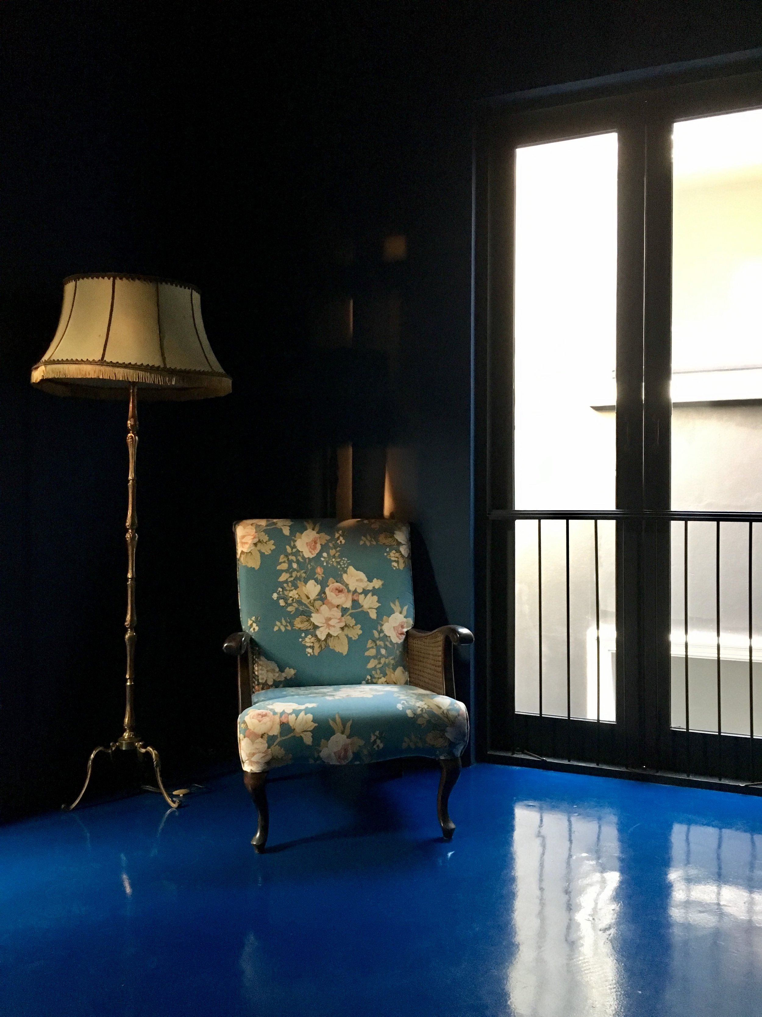 A bright blue floor and chair offer a delightful surprise at the top of the stairs