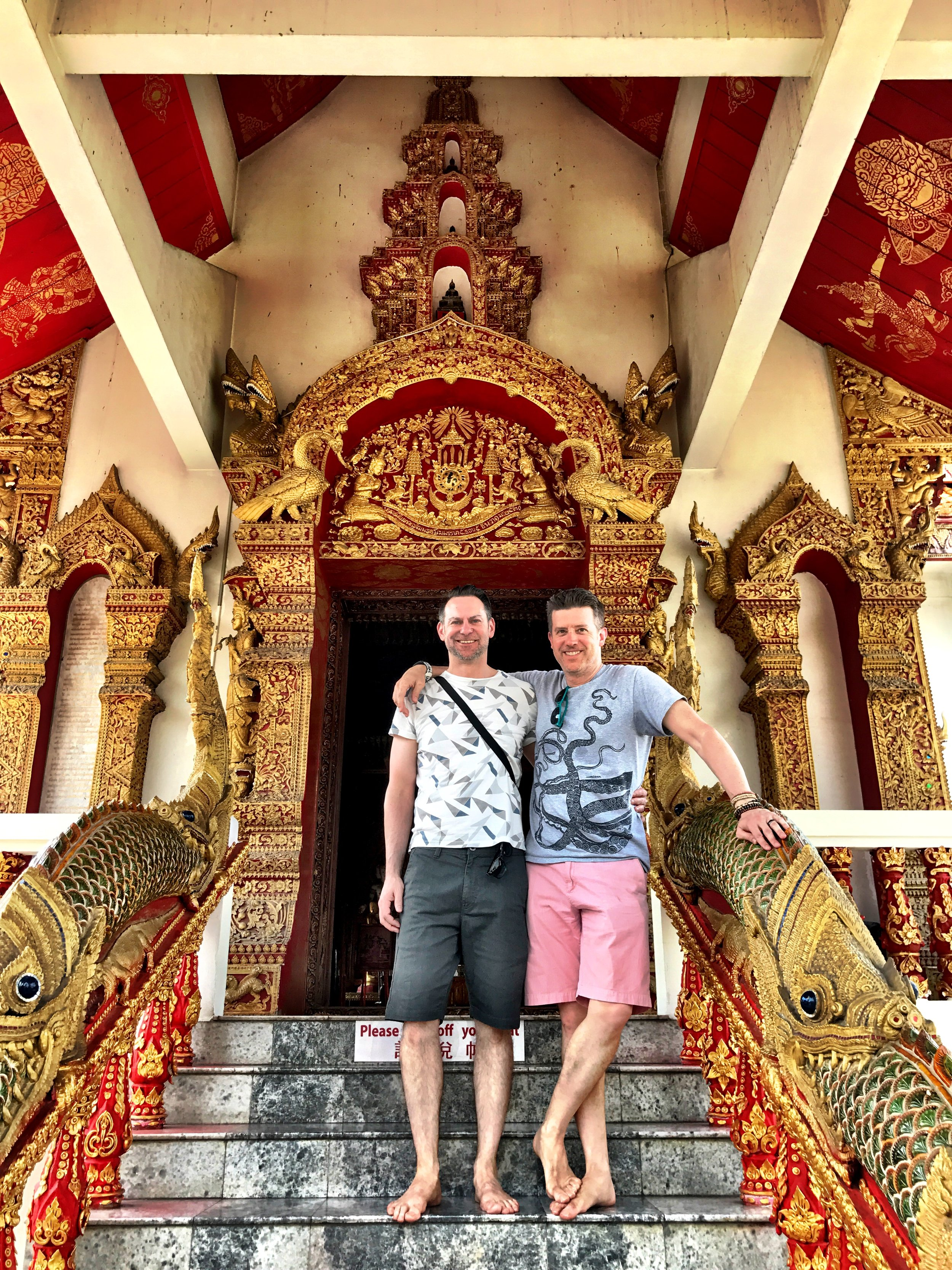 Duke and Wally on the steps of the Dhamma Hall at Wat Bupphrama, resplendent in deep red with elaborate gold details