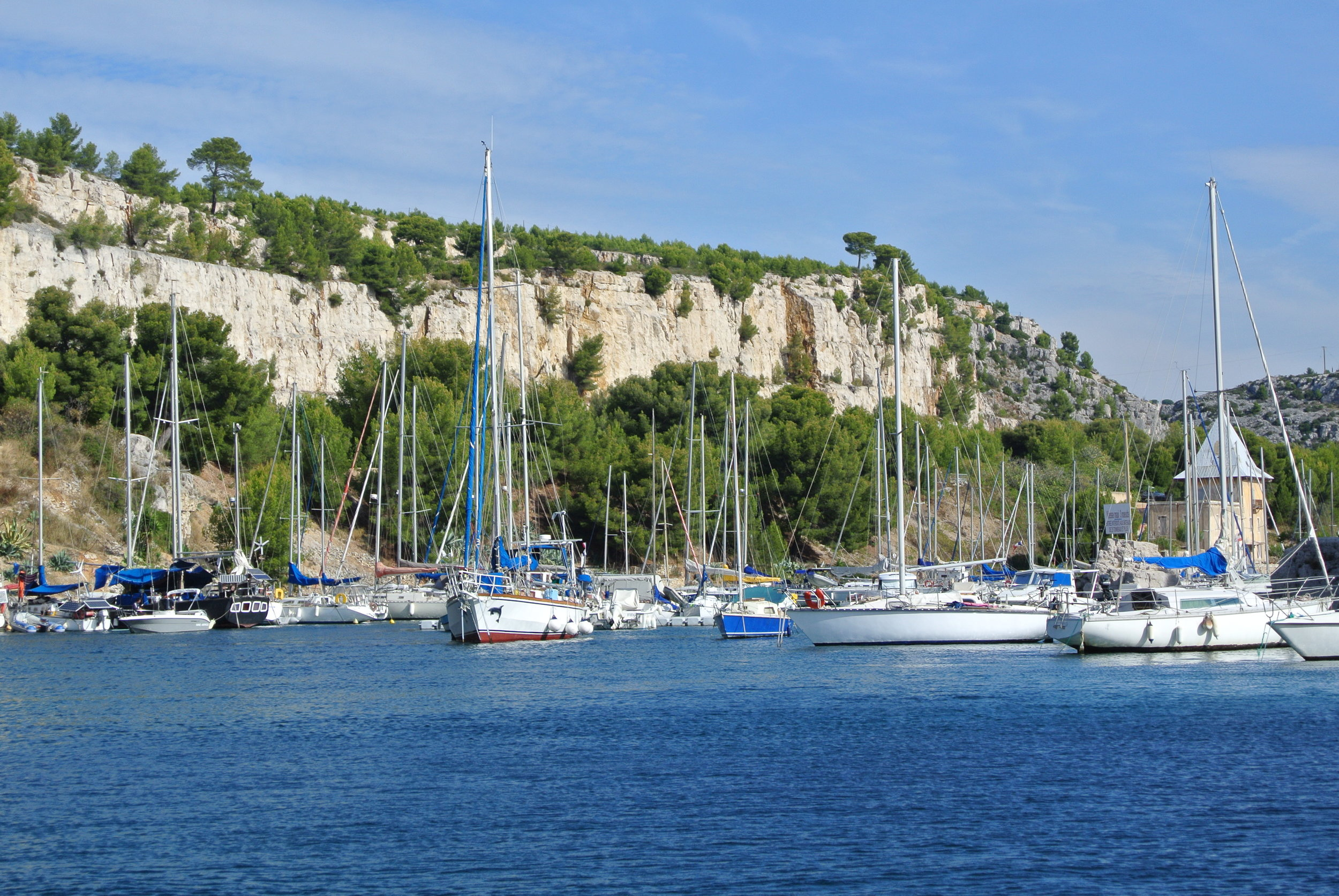 The Port of Cassis on the French Riviera, with its pretty backdrop of the limestone cliffs called calanques