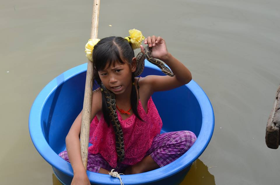 A girl bobbing along in a plastic wash basin with a snake around her neck, begging for money for having her photo taken