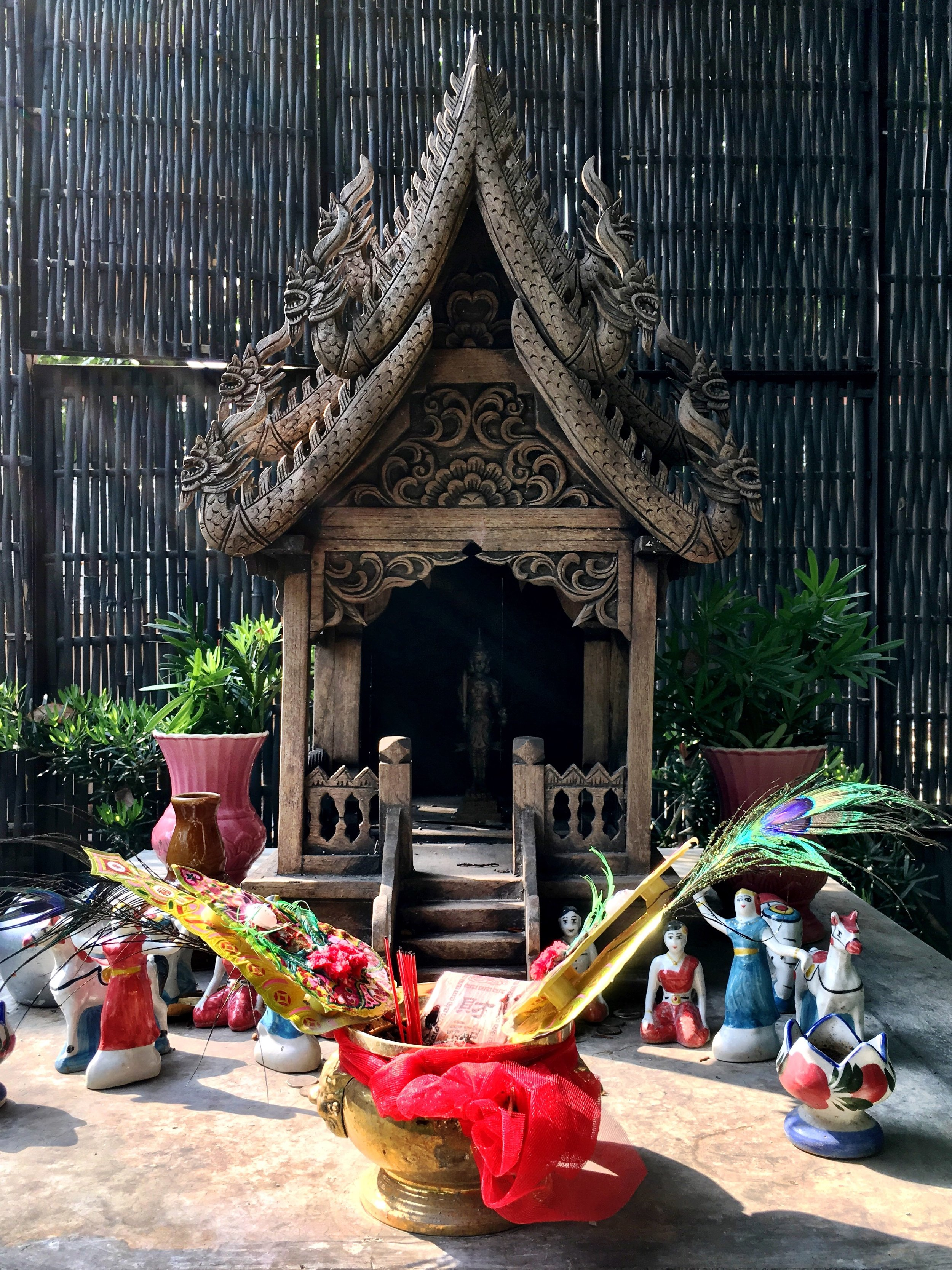 Wally and Duke gave offerings of fruit and said prayers at the spirit house on the grounds of their hotel