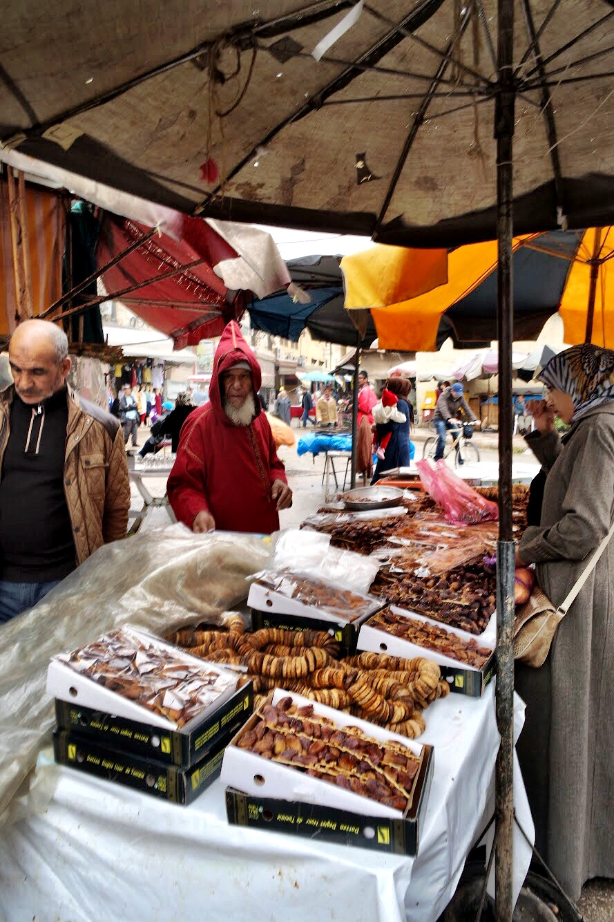 A woman sells dates off of the main square