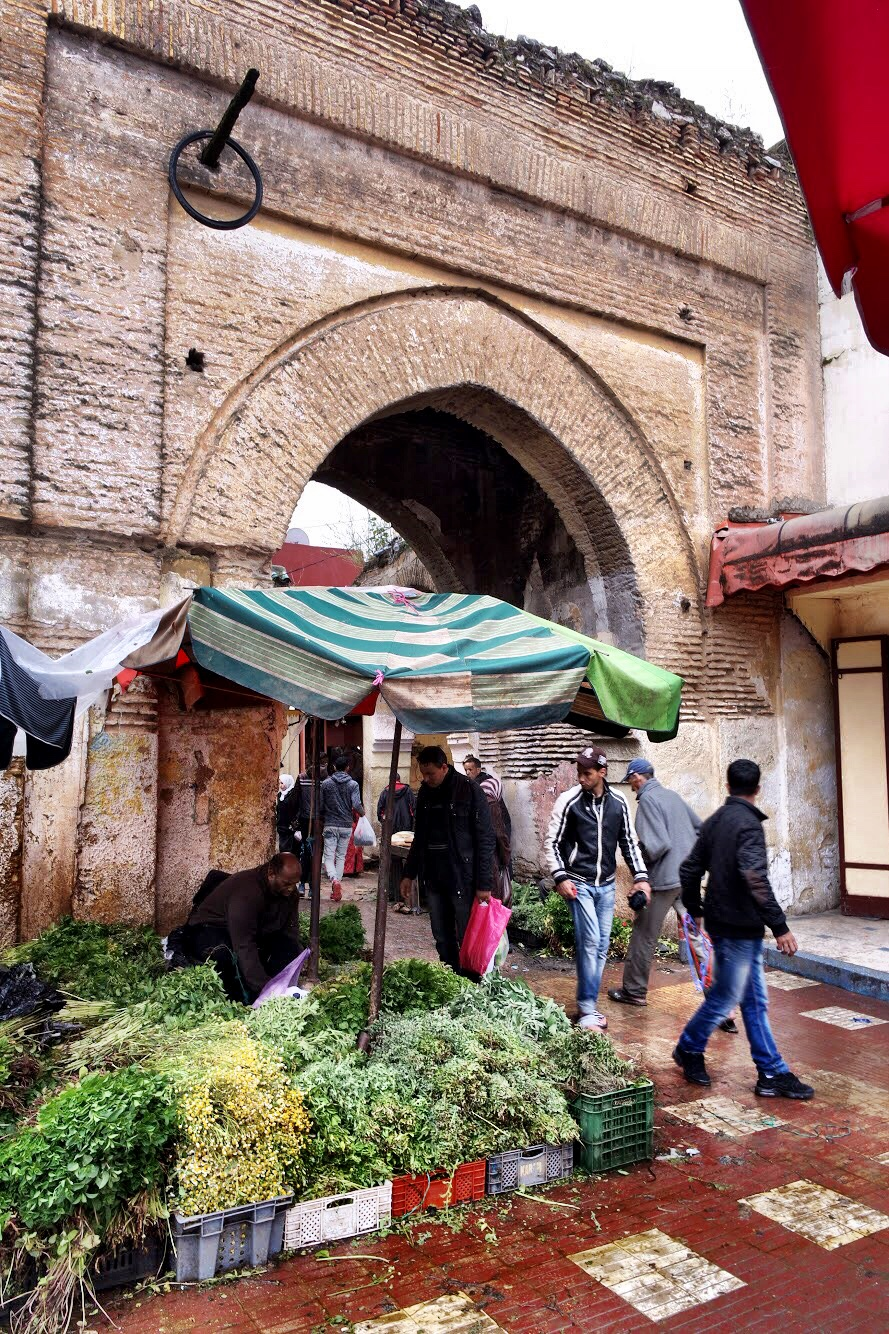 A vendor sells greens near one of the arches of the old city