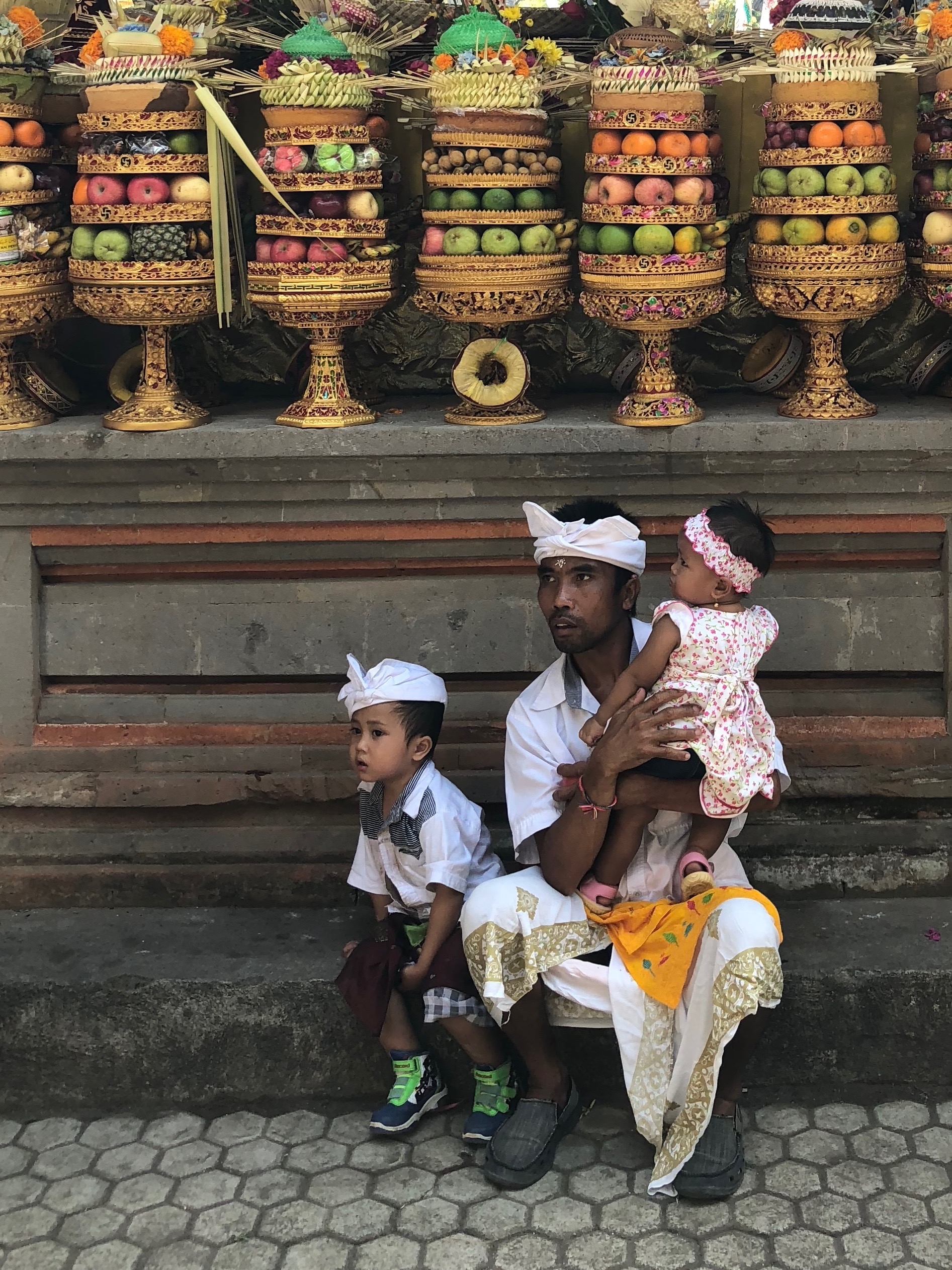 A man and his children pause under the elaborate temple offerings