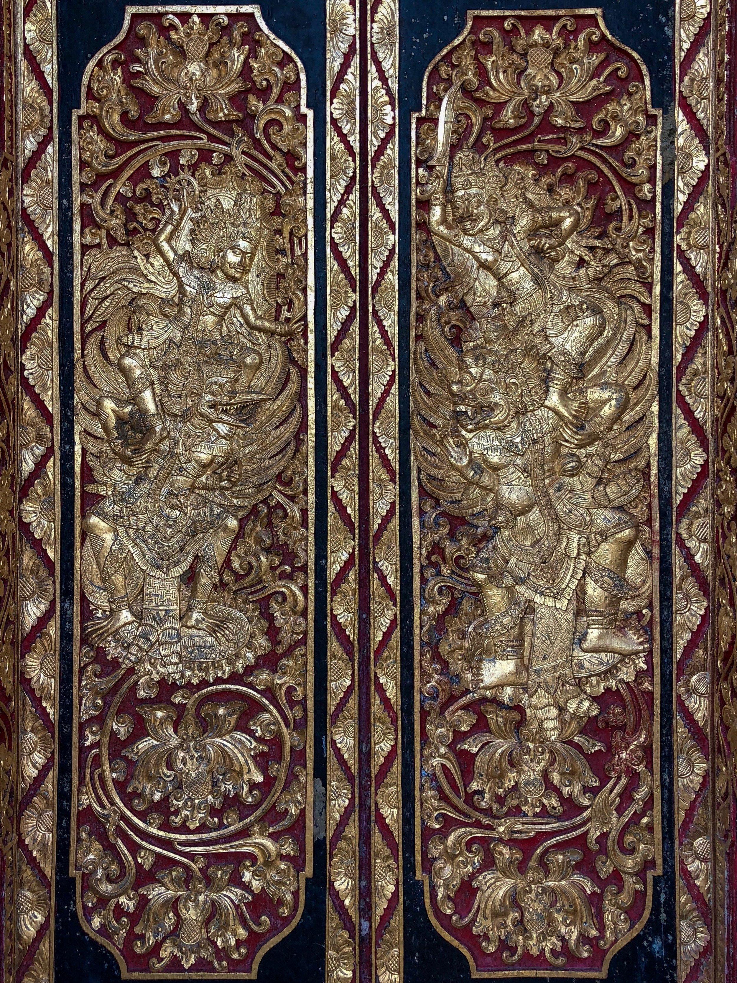 The door detail on the entrance gate shows the god Vishnu, riding his eagle mount Garuda and battling a pair of  rakshasa  demons