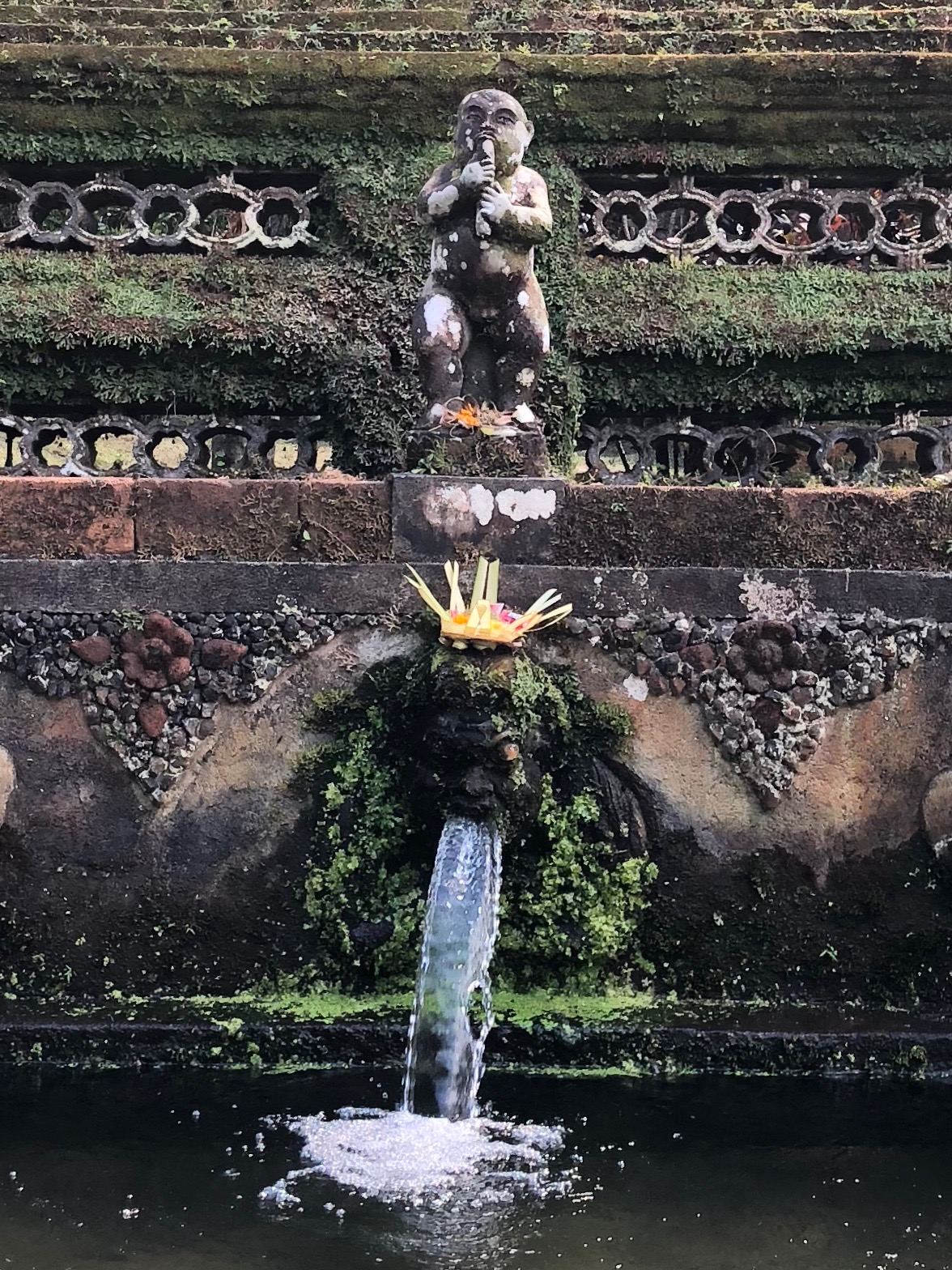 Water pours from the weatherworn carved faces in the bathing pools