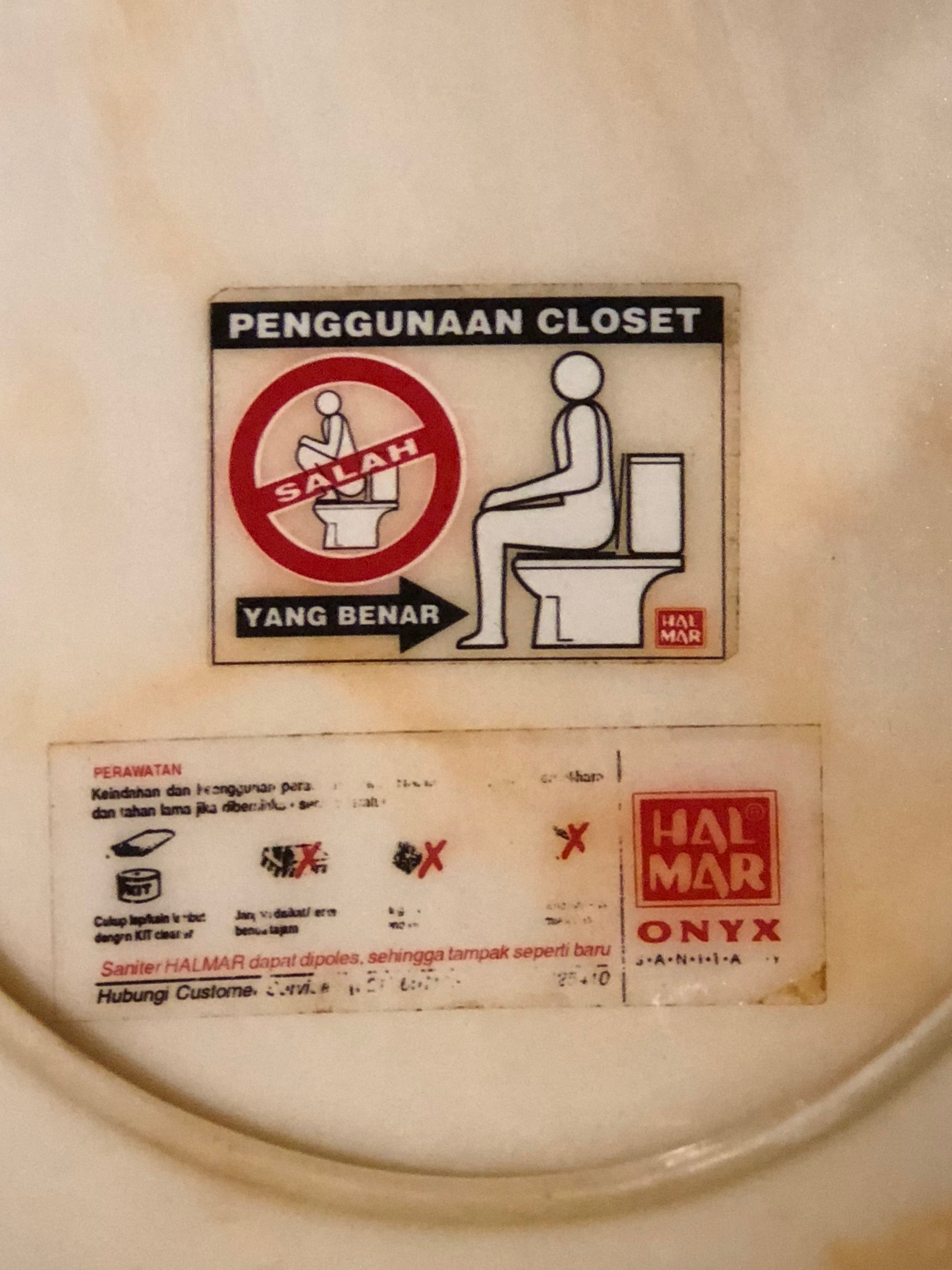 The only time I saw Western toilets on Bali in 2001 was at hotels (usually series of bare-bones but dirt-cheap villas). This sticker showing people how to use them — don't squat right on the seat! — never failed to amuse me