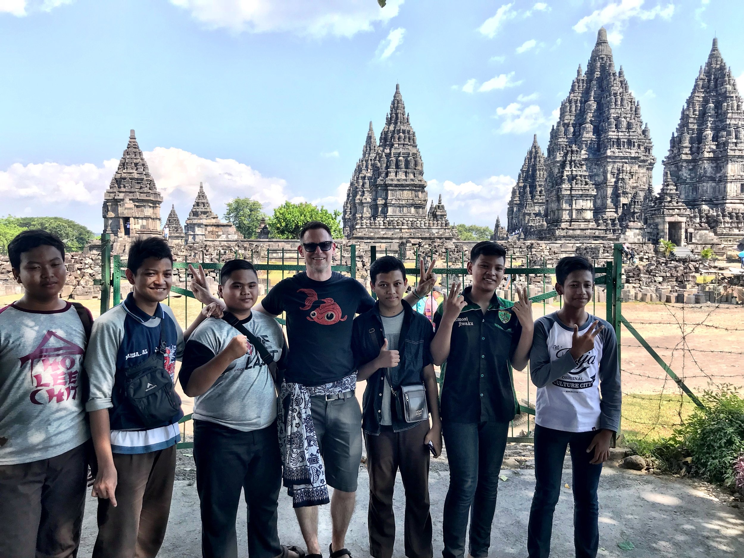 Duke poses with a group of local boys, with Prambanan behind them, looking like a fake backdrop