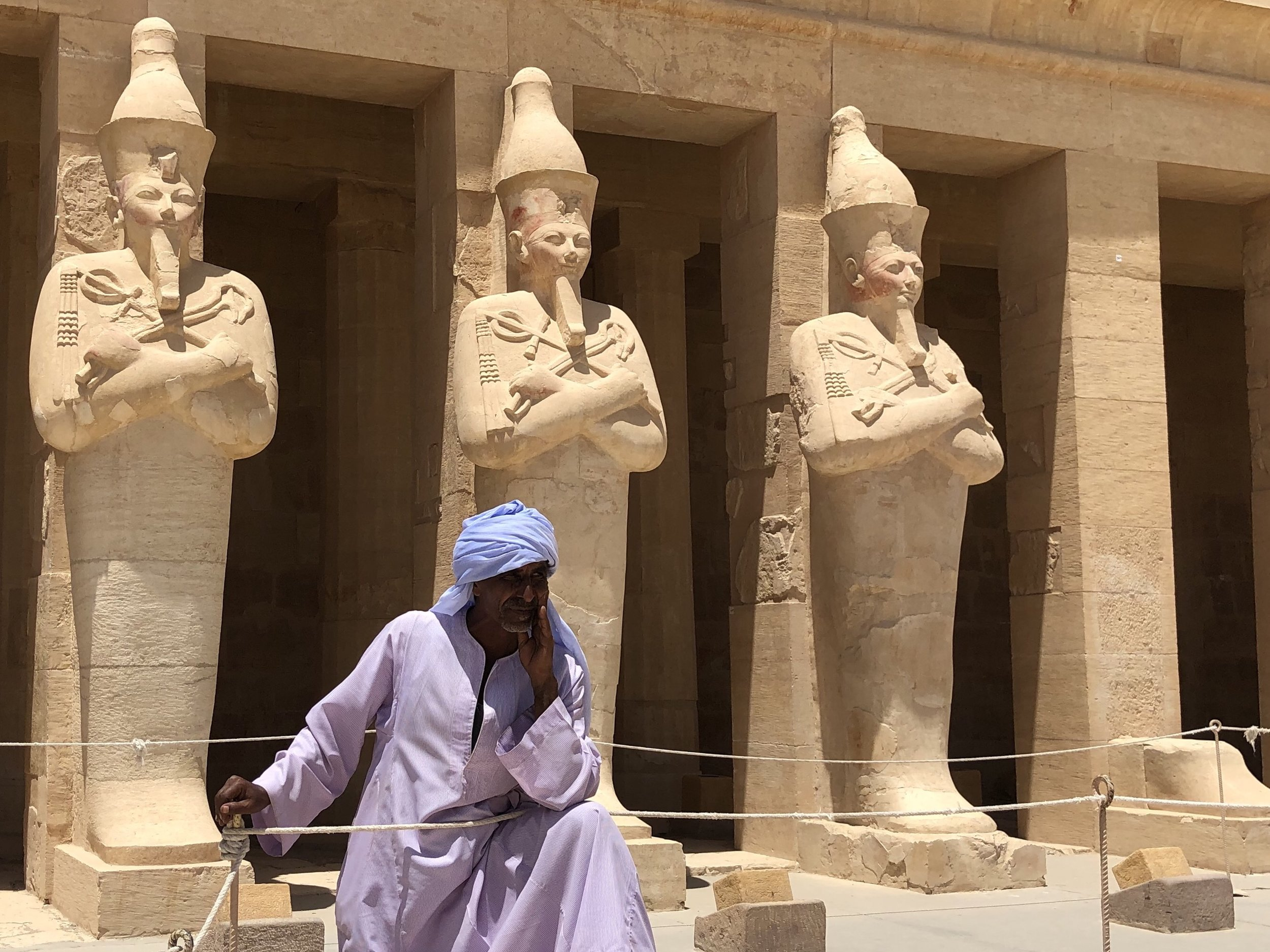 A temple employee in front of some of the statues — note the reddish color on their faces