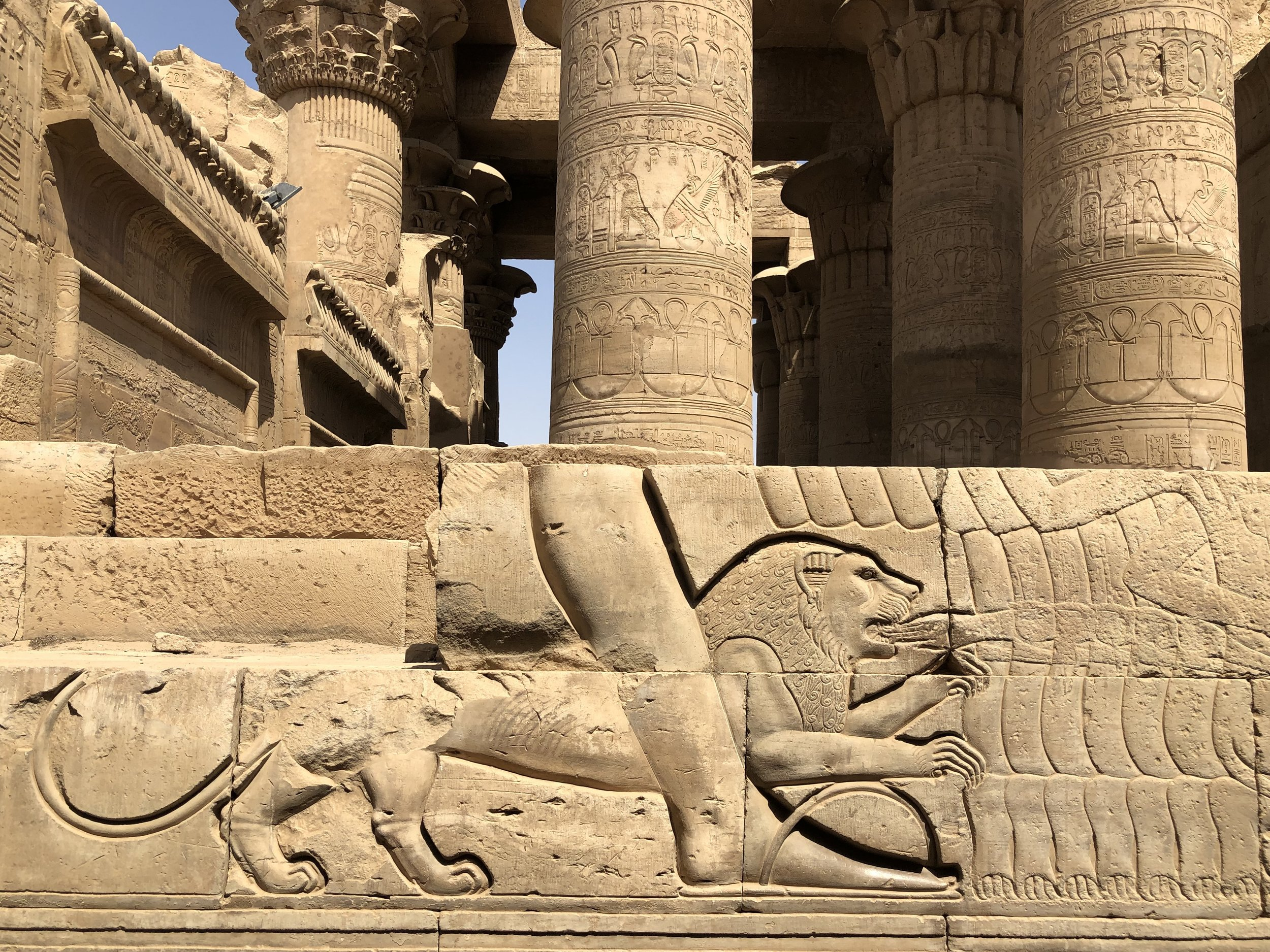 On one side of the temple's exterior, a lion bites a hand
