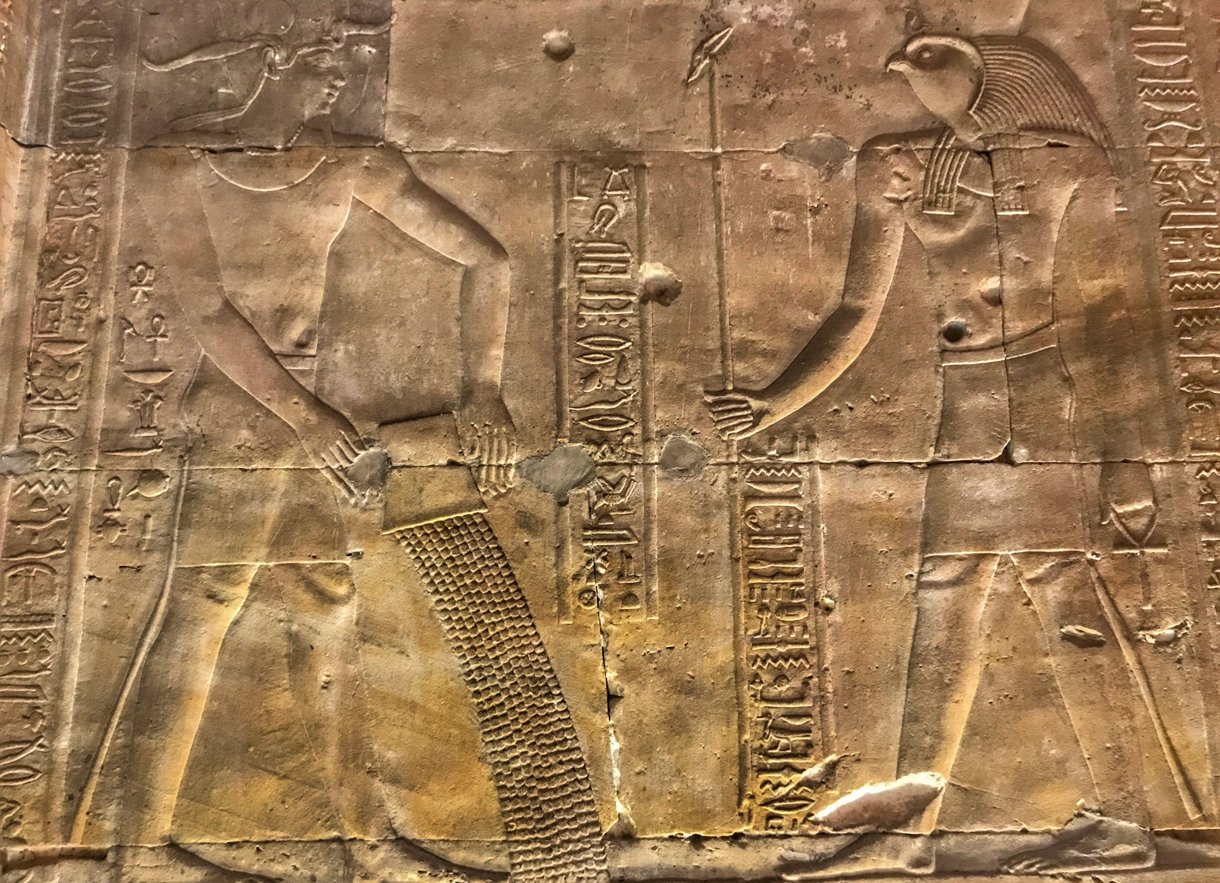 The figure on the left pours out holy water in front of Horus