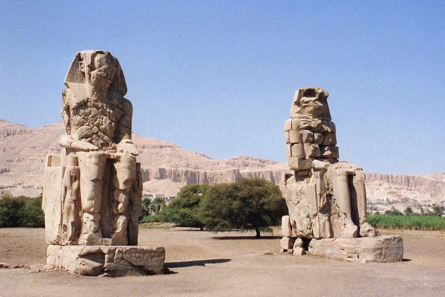The Colossi of Memnon stood as they do today, in a clearing surrounded by fields. But there were no barriers of any kind — you could climb the statues if agile enough
