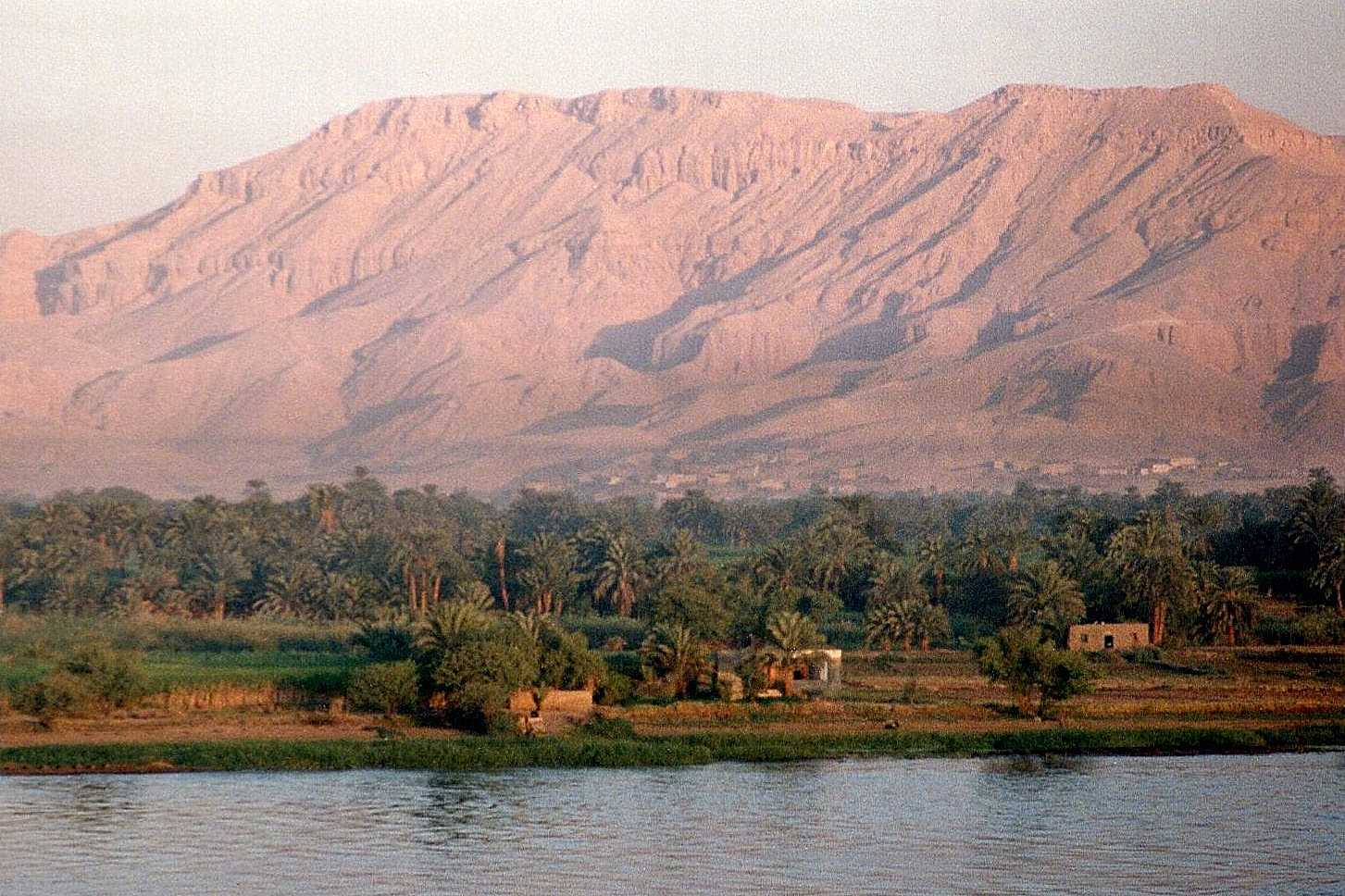 The rising sun turns the Theban mountains pink. As you can see, the West Bank was entirely agricultural. Luxor had yet to jump the river