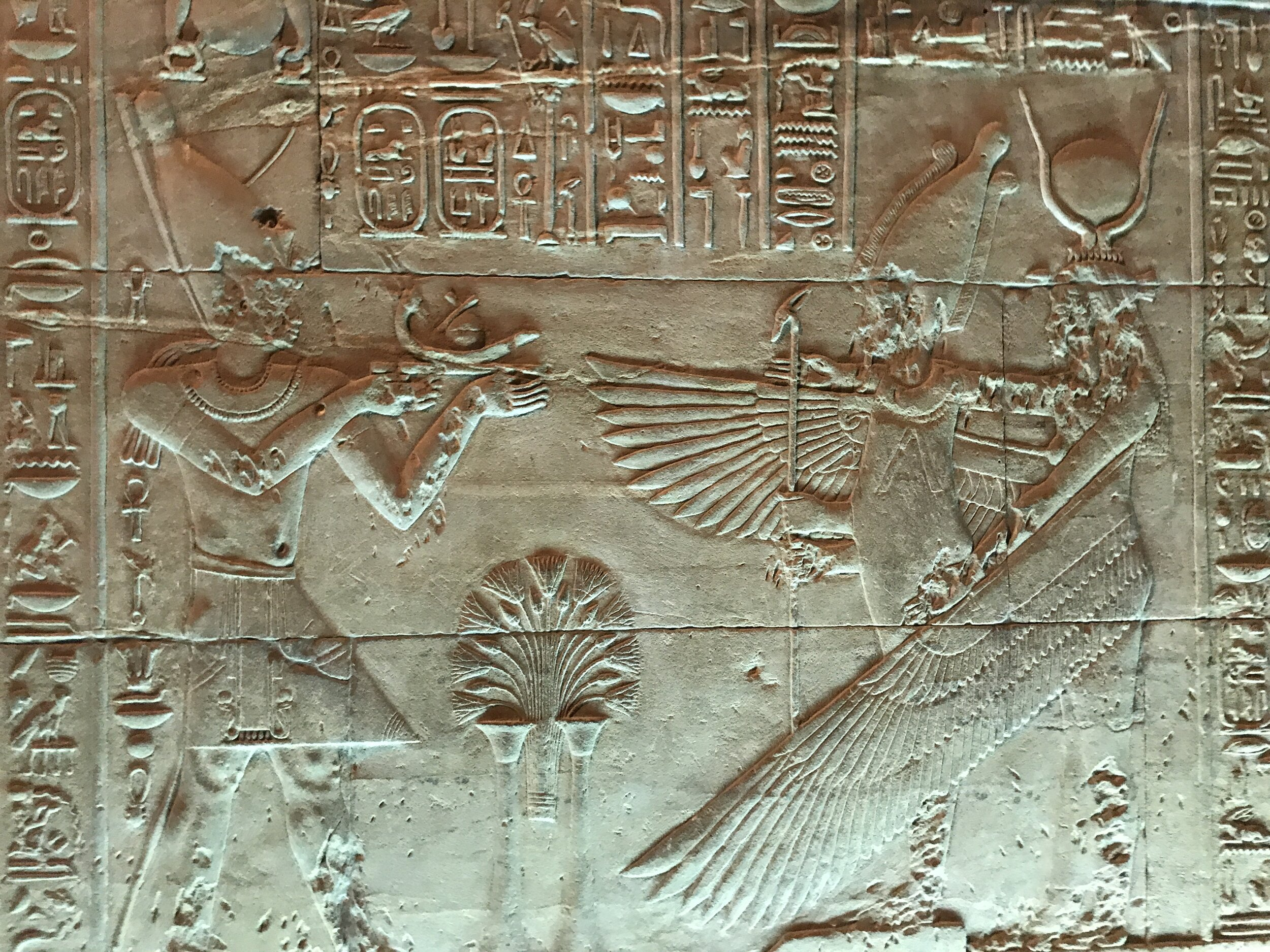 One of the Ptolemaic pharaohs presents an offering to the goddess Isis, with her massive wings