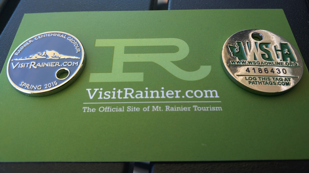 Front and back of series one pathtag sitting on top of a Visit Rainier business card