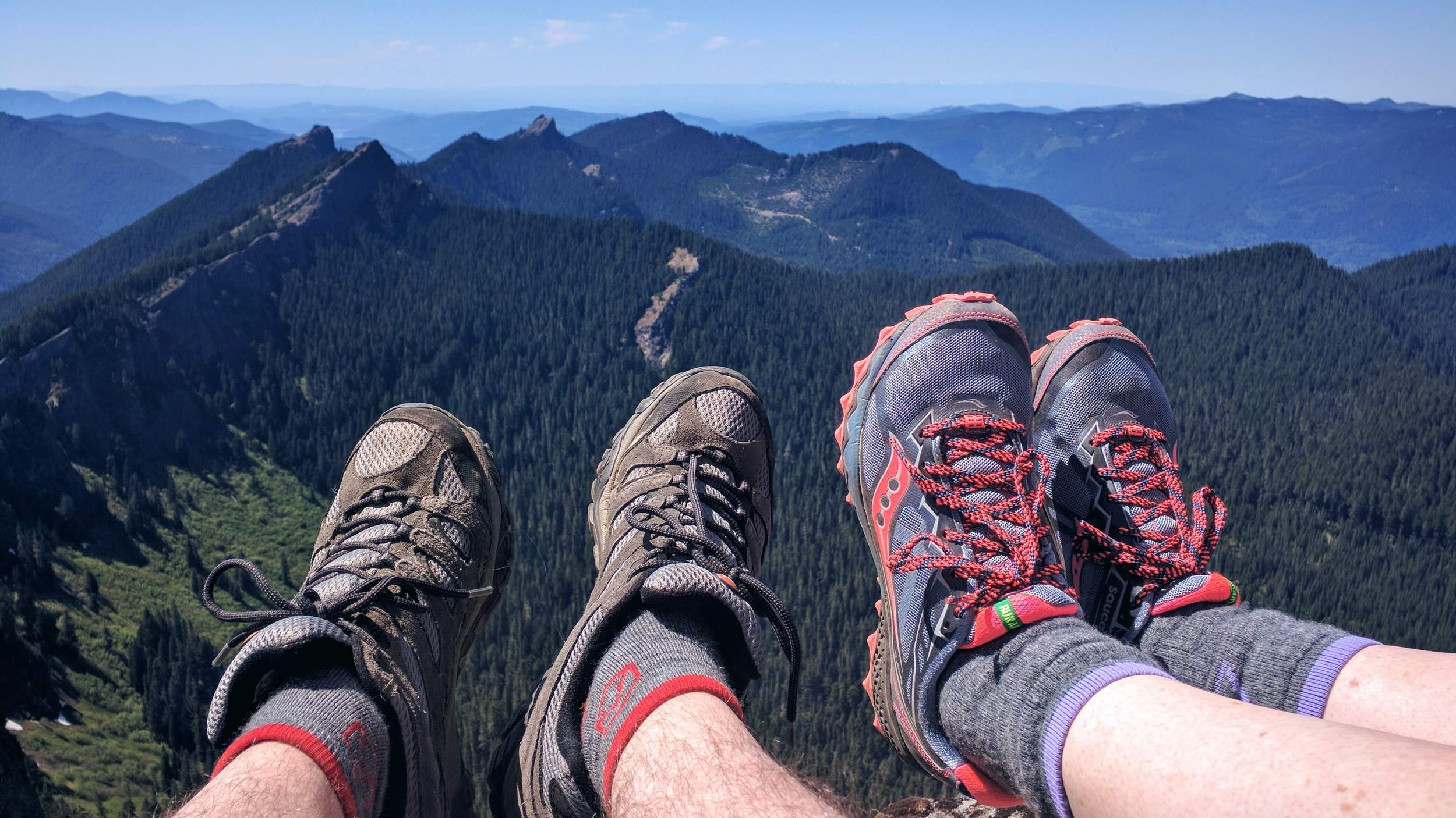 Feet Dangling Over High Rock with Sawtooth Ridge in the Distance