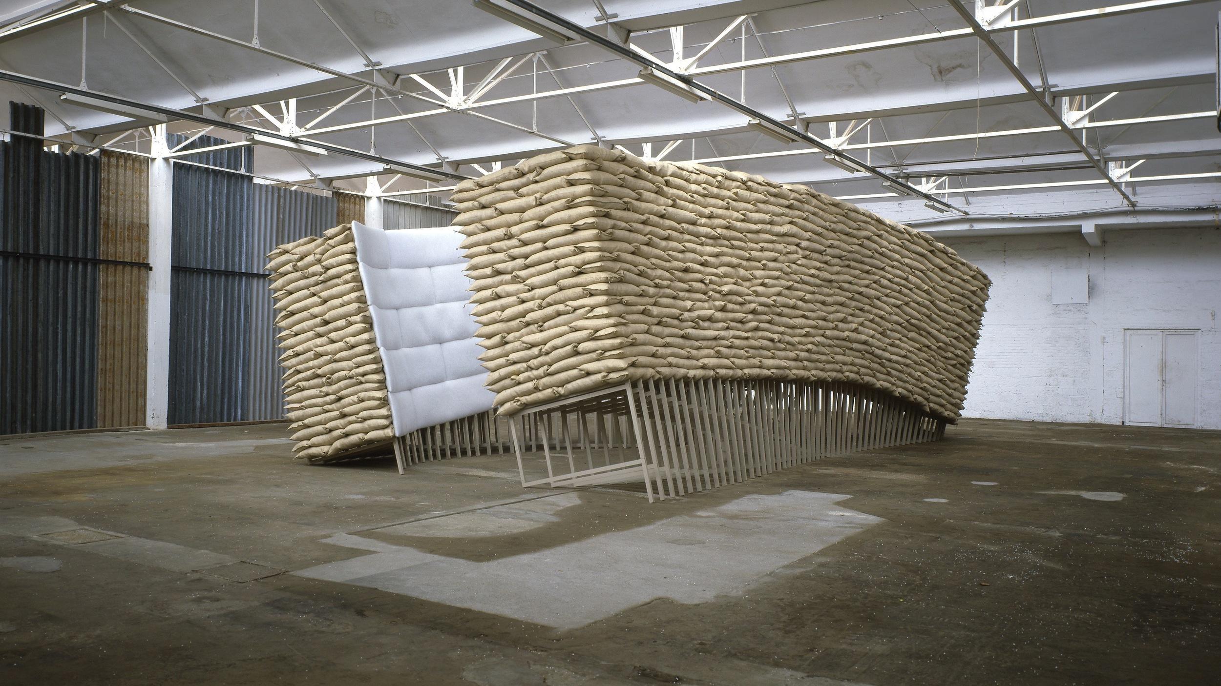 Nancy Turlington, 1994 , wood, sandbags, putty, upholstery, 372 x 604 x 1221 cm. Installation view at Kanaal, Kortrijk, Belgium