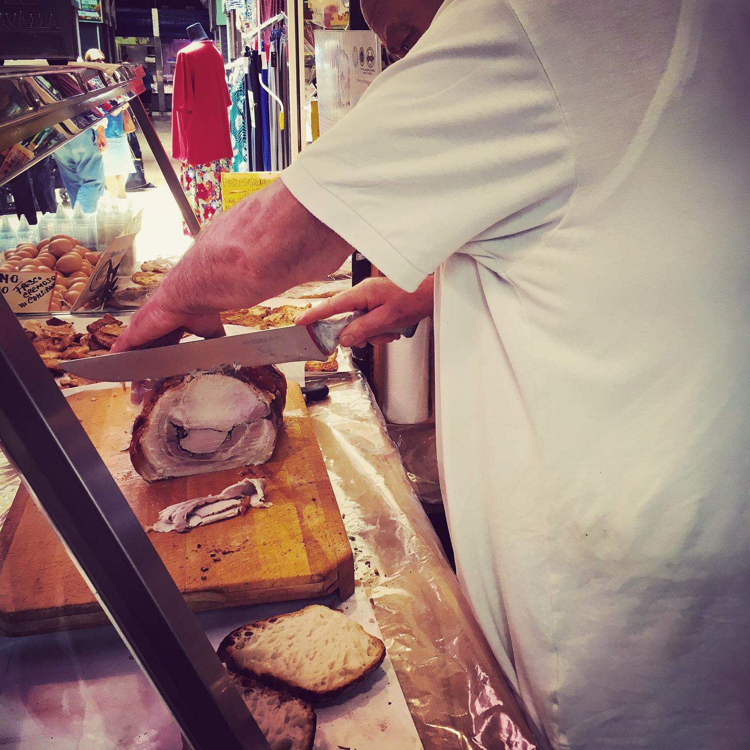 Knife-wielding man preparing a panino di porchetta