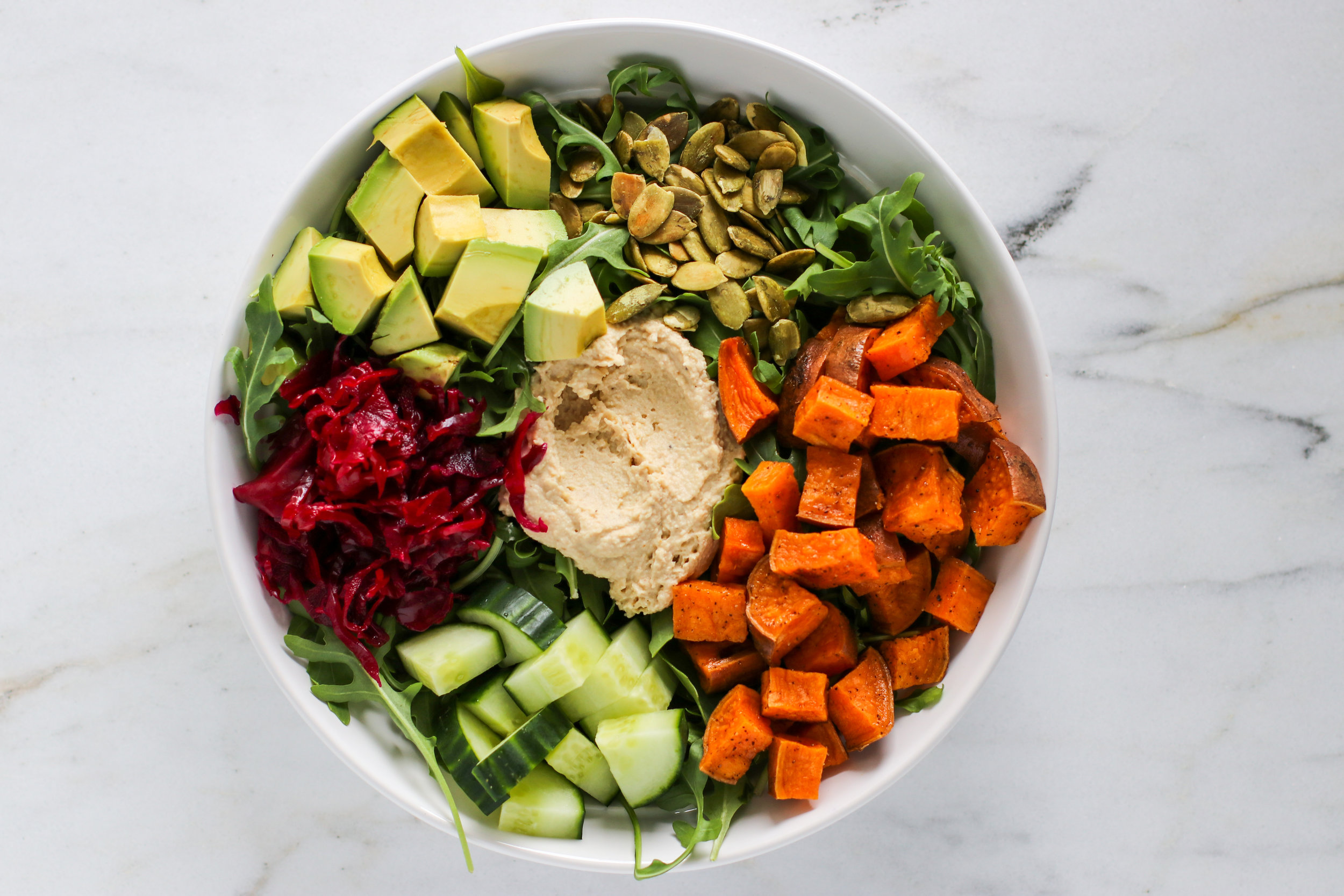 Salad Bowl #2 - An arugula base topped with avocado, pumpkin seeds, roasted sweet potatoes, cucumber, ruby kraut, and a big dollop of hummus.I dress my salads very lightly, and I find that the hummus, avocado, and kraut usually provide enough to coat the rest of the veggies.
