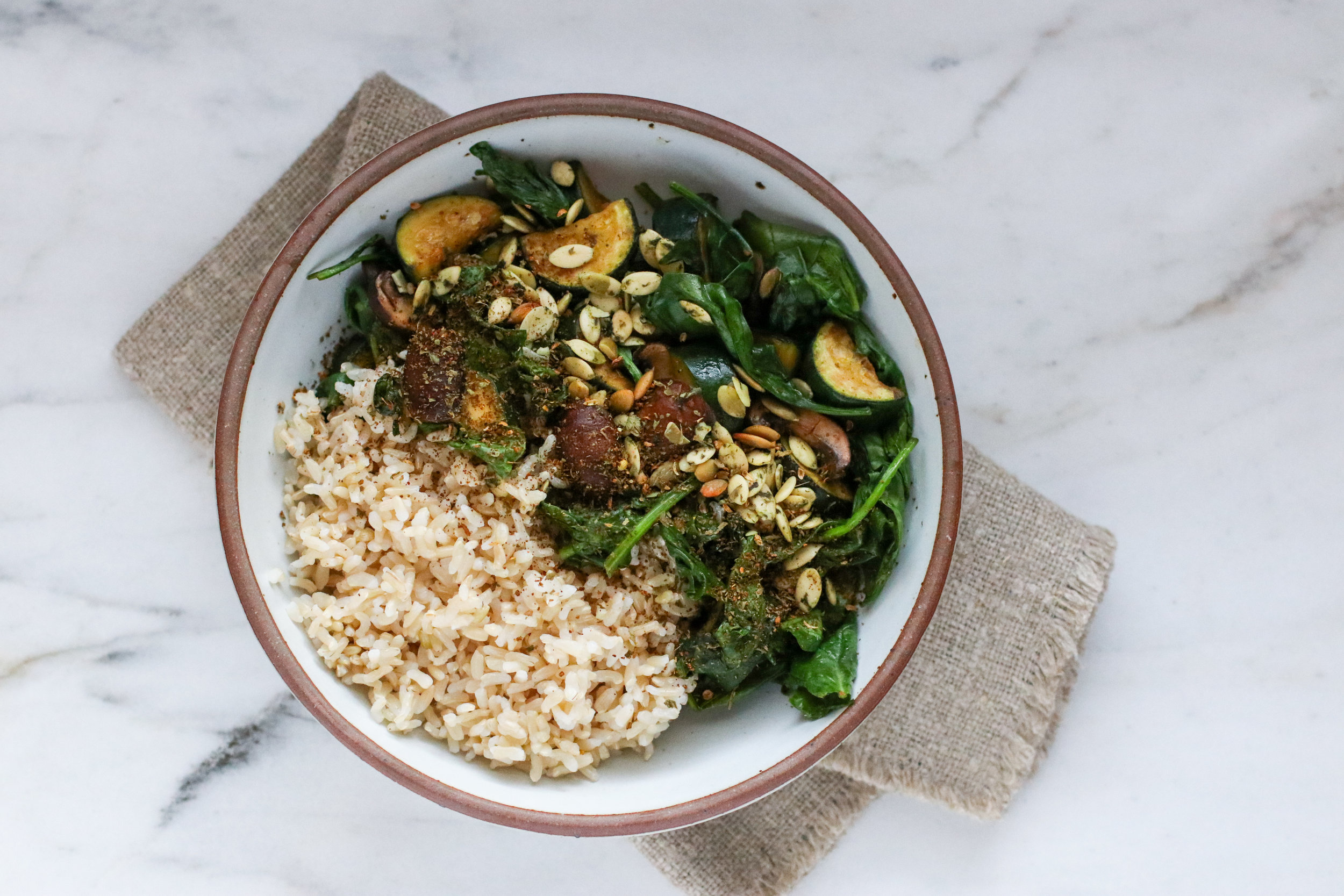 Brown Rice + Sautéed Mushrooms + Zucchini + Spinach all topped with Pumpkin Seeds