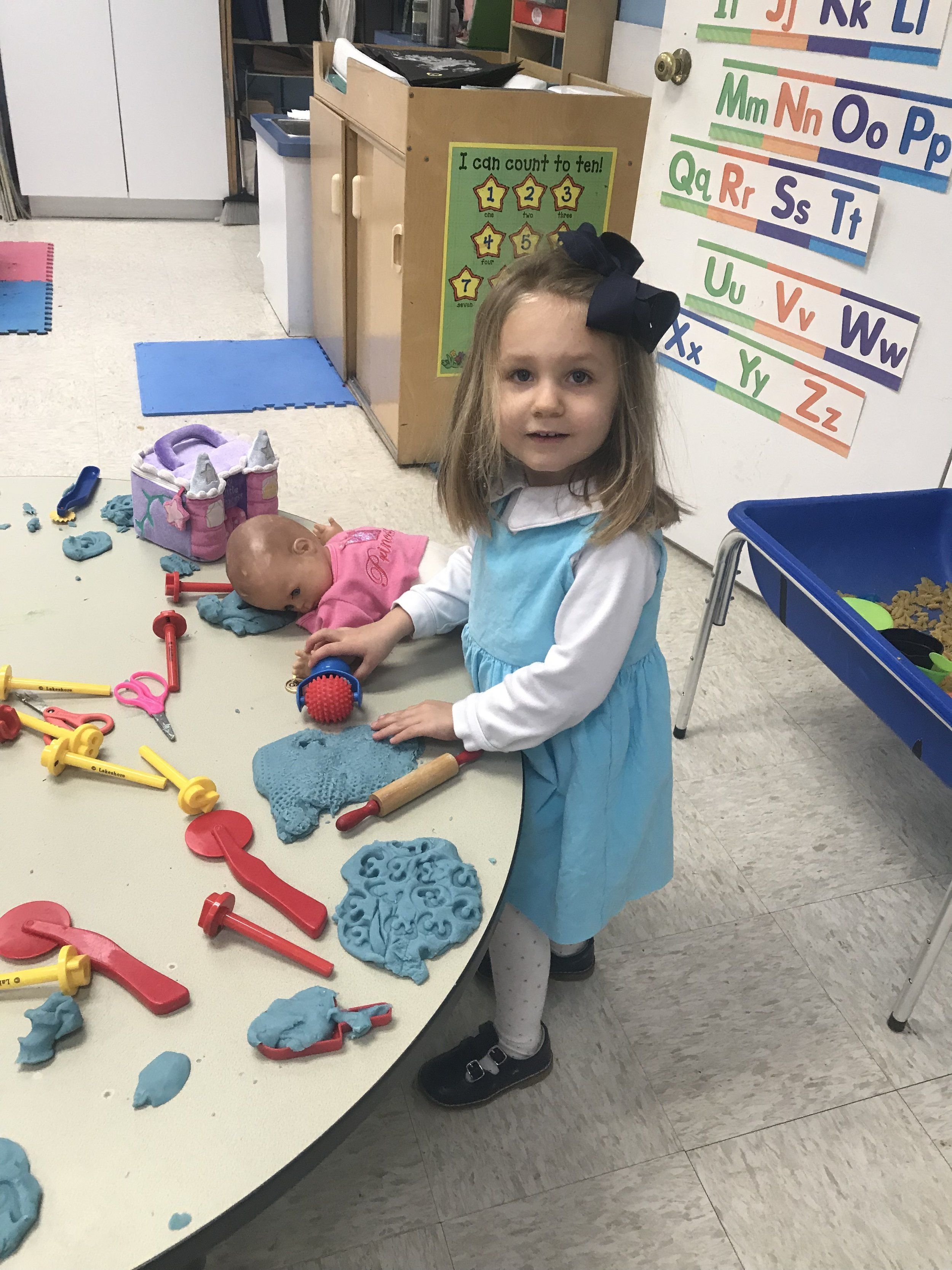 """Mary Witt """"rolling out some pizza"""" with play-doh."""